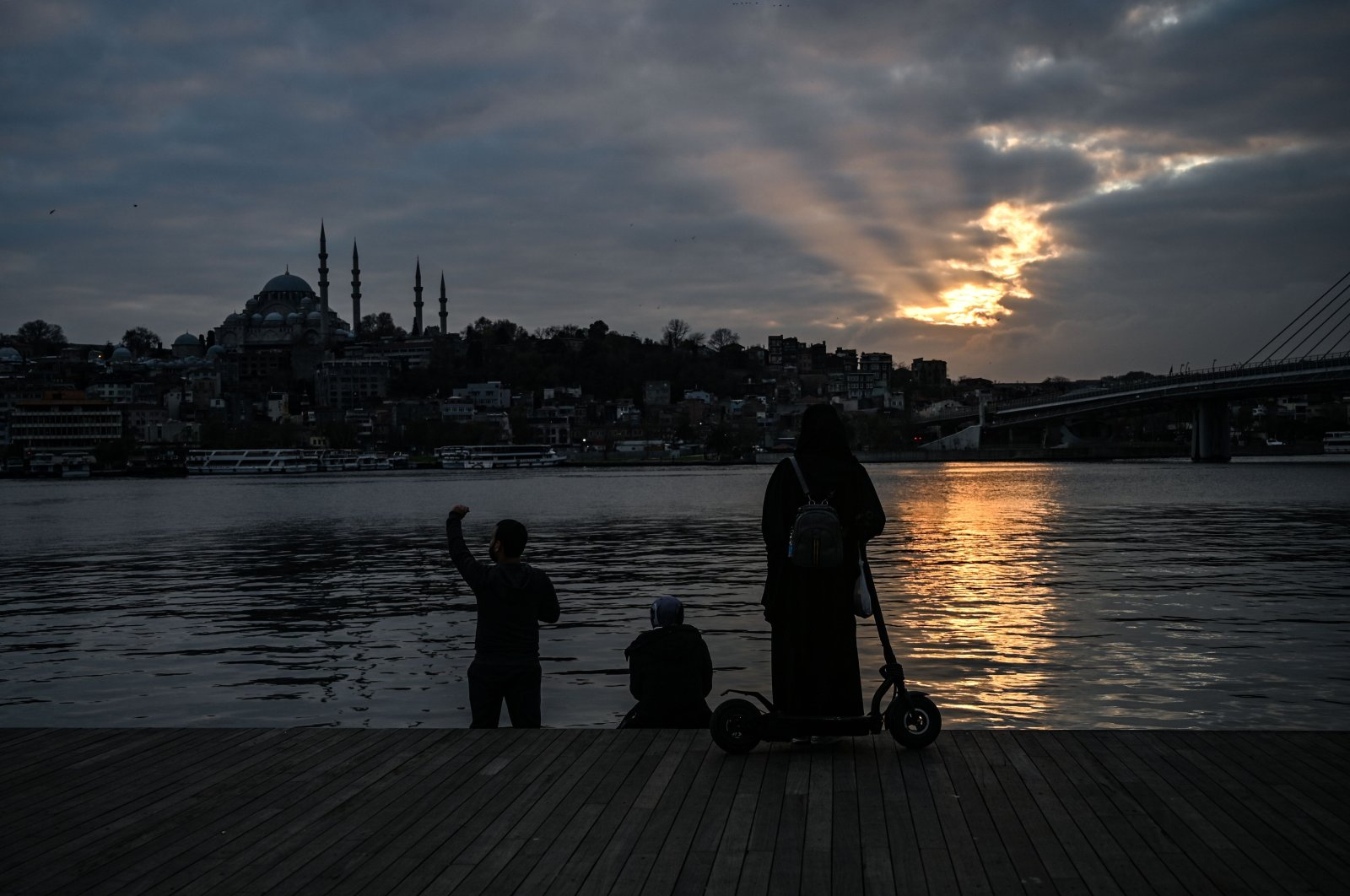 People look at the sunset from the deserted shore of the Golden Horn near the Karakoy district, in Istanbul during a week-end curfew, aimed at curbing the spread of the COVID-19 pandemic caused by the novel coronavirus, on Dec. 19, 2020. (AFP Photo)