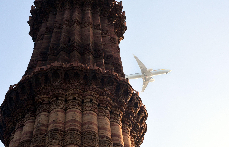 An airplane flies near Qutb Minar in New Delhi,India, on Dec. 18, 2020. (AA PHOTO)
