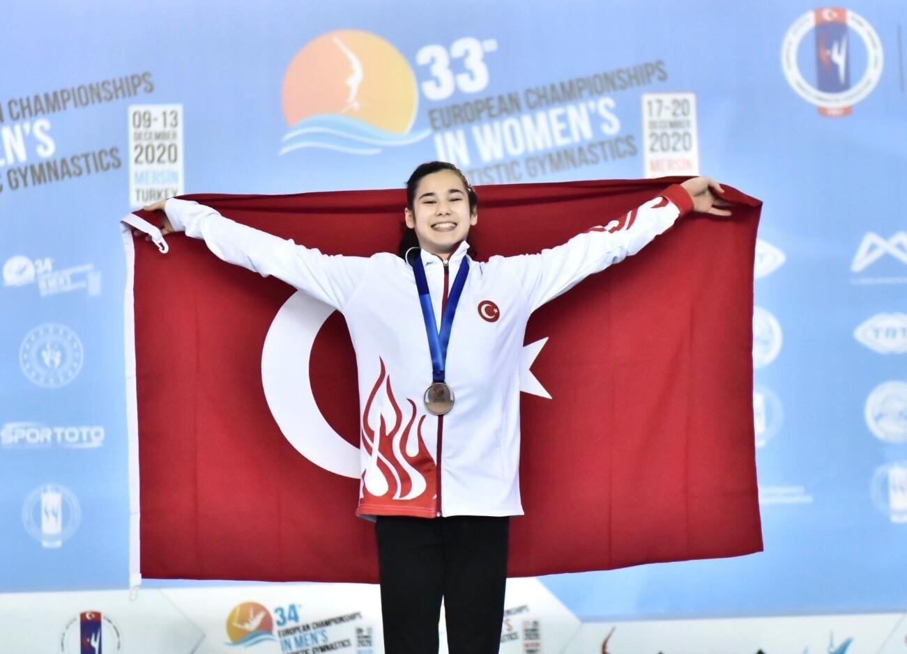 Turkish gymnast Derin Tanrıyaşükür poses for a photo holding a Turkish flag after winning a bronze medal at the competition, Dec. 20, 2020. (AA Photo)