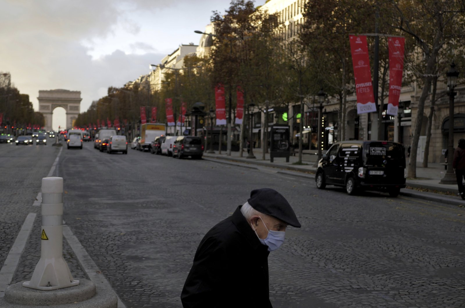 An elderly man wears a mask as he walks on the Champs Elysee in Paris, Nov. 19, 2020. (AP Photo)