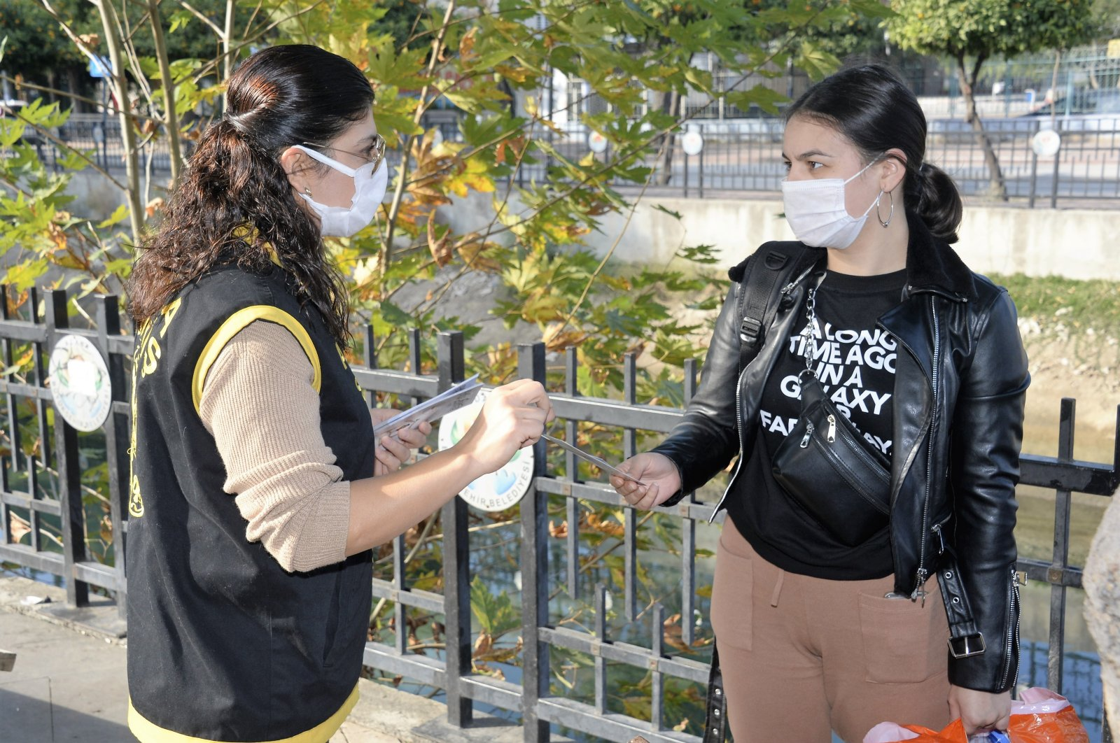 A police officer distributes leaflets on domestic violence to a woman, in Adana, southern Turkey, Dec. 16, 2020. (IHA Photo)