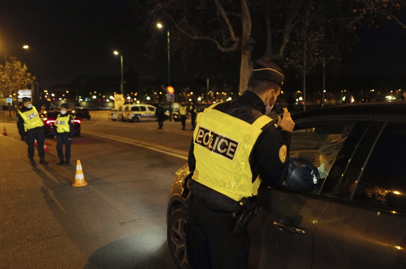 French police officers check a car near the National Assembly as they enforce a coronavirus-related curfew, in Paris, France, Dec. 15, 2020. (AP Photo)