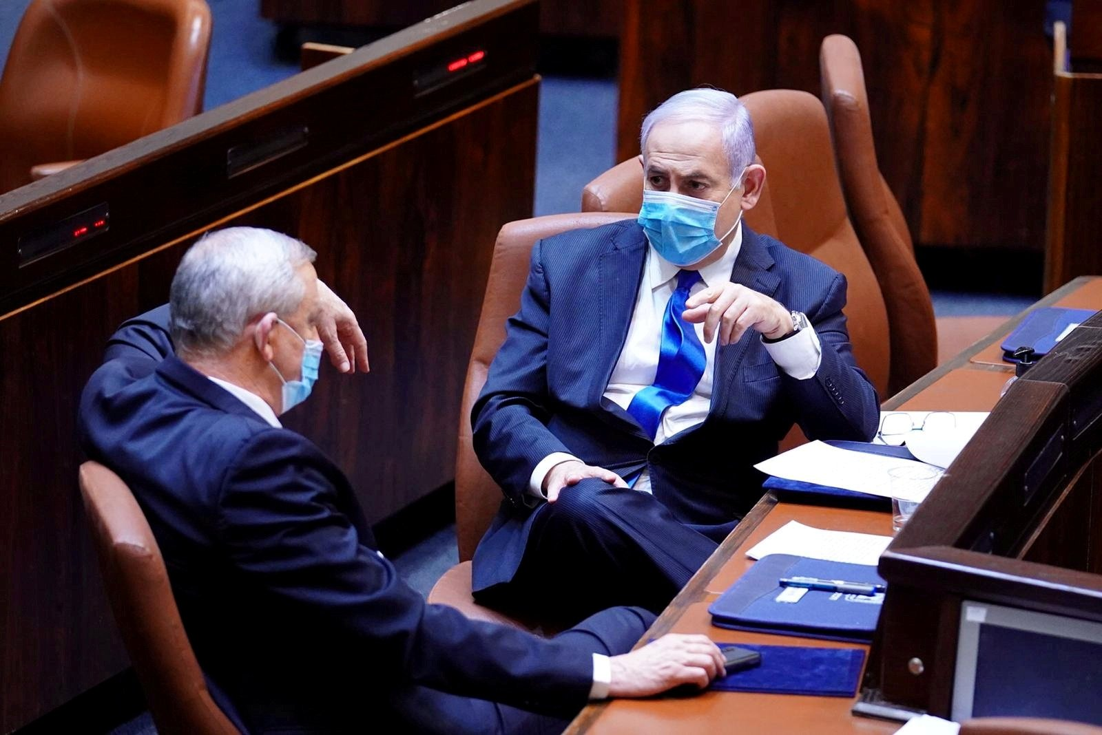 Israeli Prime Minister Benjamin Netanyahu (R) and Benny Gantz, centrist Blue and White leader and Netanyahu's partner in his new unity government, wear face masks as they talk during a swearing-in ceremony of the new government, at the Knesset, in Jerusalem, May 17, 2020. (Amos Ben Gershon/Knesset Spokesperson's Office Handout via Reuters)