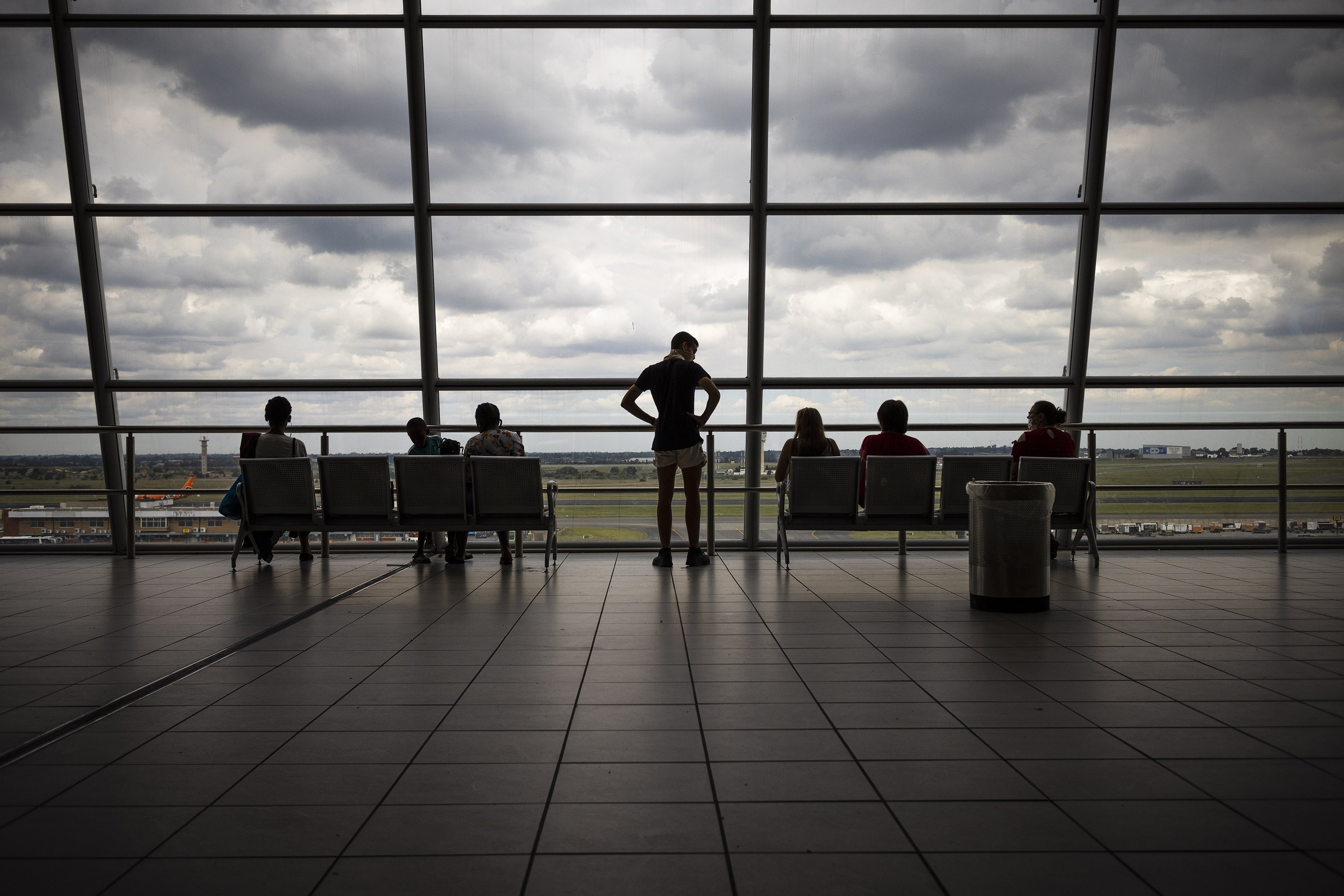 epa08897779 Passengers sit and watch aeroplanes take of and land from the observation deck at the OR Thambo International airport, Johannesburg, South Africa, 21 December 2020. Israel, Turkey, Germany, Saudi Arabia, and Switzerland have all halted air travel to and from South Africa as other airlines cancel flights from the United Kingdom as both countries are showing cases of a new varient of the Corivd-19 Corona virus 501.v2, a mutated SARS-CoV-2 variant which holds a higher transmission rate. The wave of cancellations impacting the UK is likely to extend to South Africa, as countries try and keep new, possibly more virulent, variants of the coronavirus out.  EPA/KIM LUDBROOK