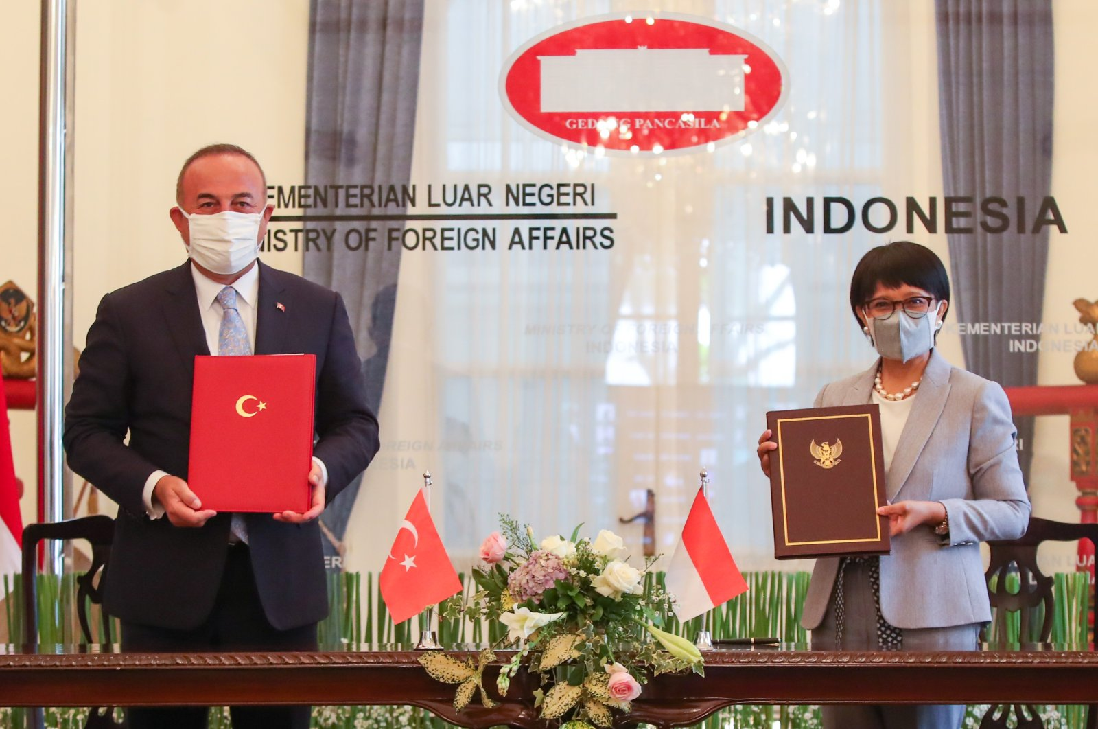 Turkey's Foreign Minister Mevlüt Çavuşoğlu (L) and his Indonesian counterpart Retno Marsudi sign a MoU in Jakarta, Indonesia, Dec. 22, 2020. (AA Photo)