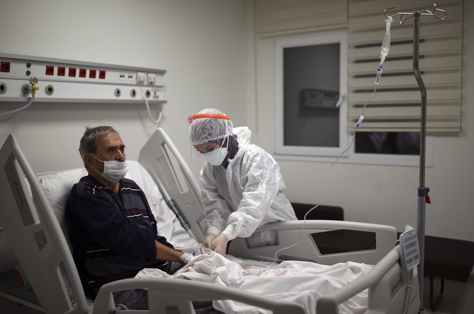 Nurse Mevlüde Altan tends to İsmail Demir infected with COVID-19, at the intensive care unit of the Prof. Dr. Feriha Oz Emergency Hospital, in Istanbul, Turkey, Dec. 19, 2020. (AP PHOTO)