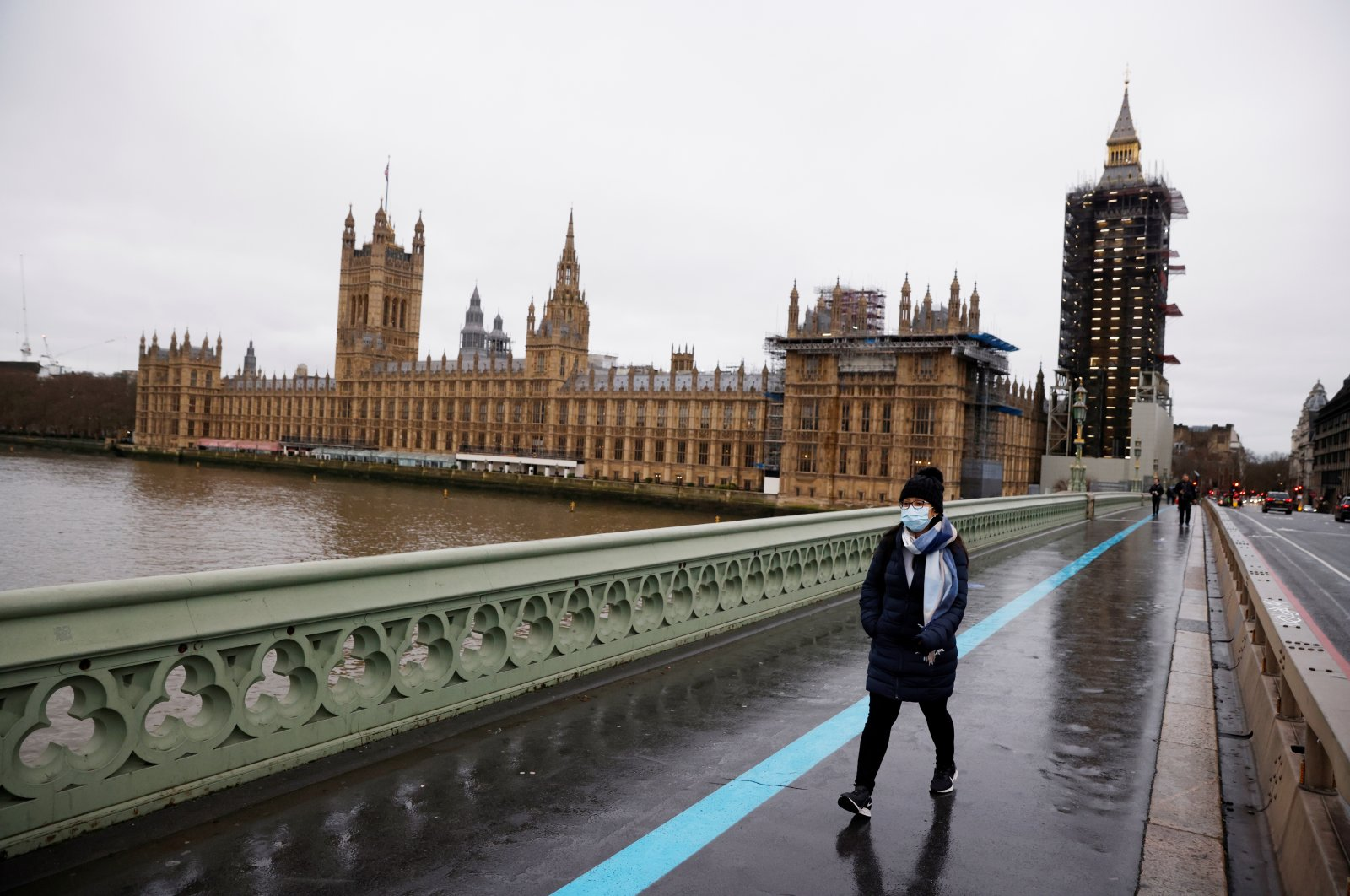 A woman wearing a mask walks across Westminster Bridge past the Houses of Parliament, as the spread of COVID-19 continues, in London, Britain, Dec. 22, 2020. (Reuters Photo)