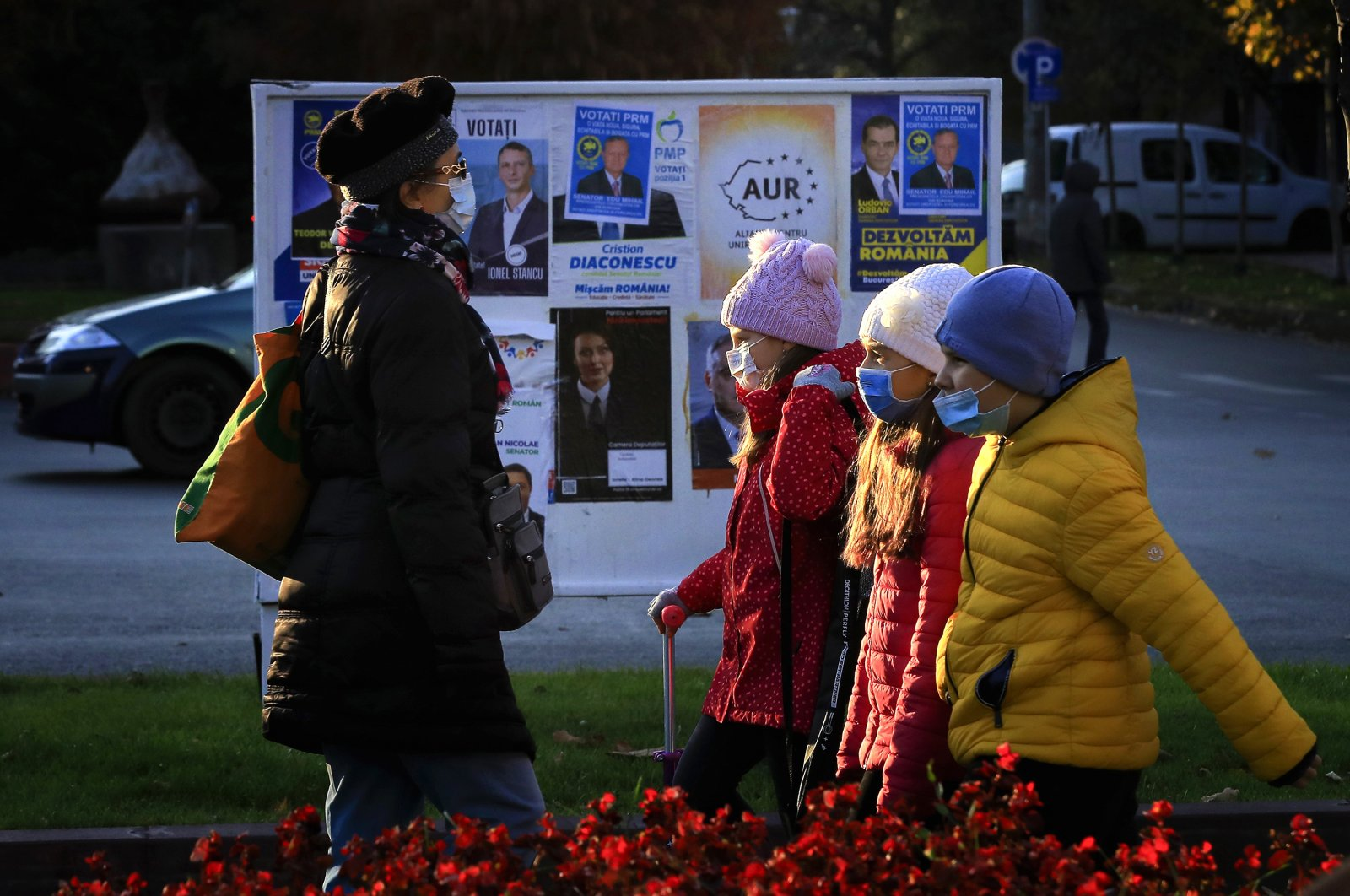 Three children and a woman (L), wearing protective masks, cross paths as they pass by a parliamentary elections campaign board in Bucharest, Romania, Nov. 23, 2020. (EPA Photo)