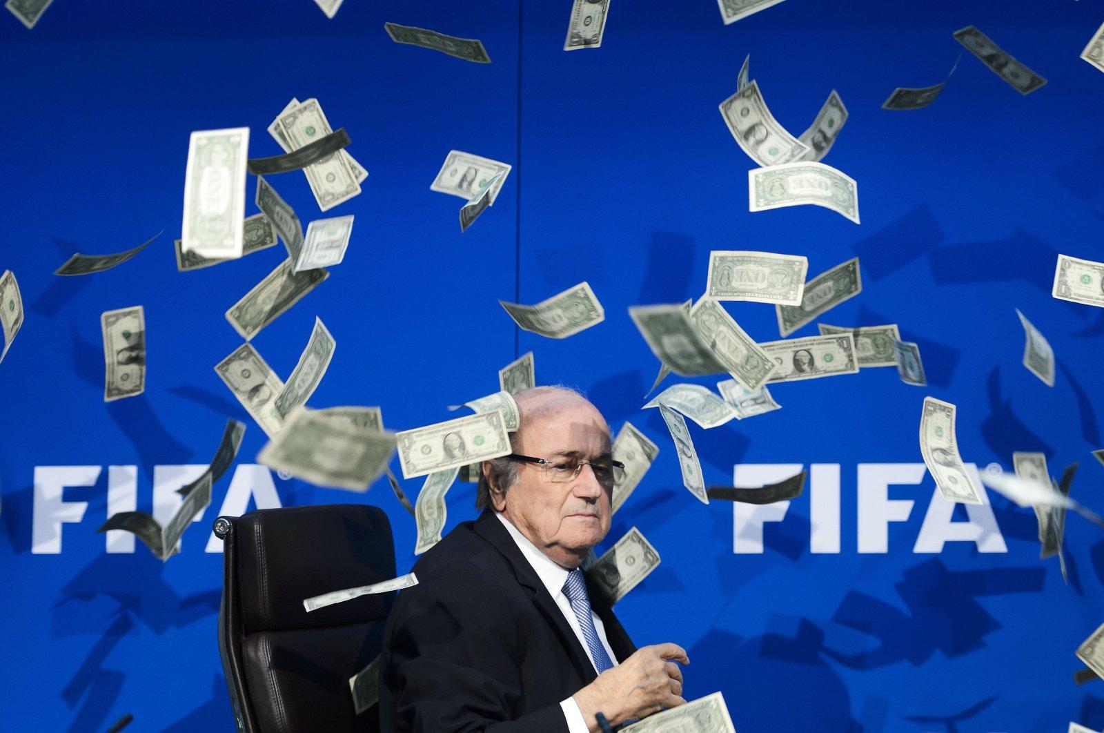 FIFA president Sepp Blatter looks on as fake dollar notes fly around him, in Zurich, Switzerland, Jul. 20, 2015.  (AFP PHOTO)