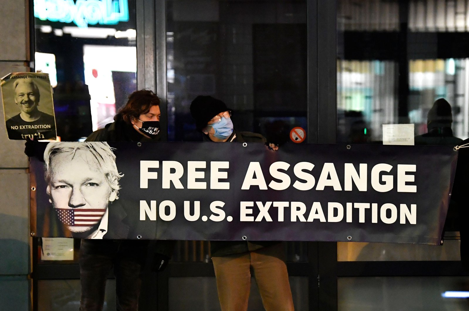 Protesters hold a sign to support WikiLeaks founder Julian Assange in front of the British Embassy in Brussels, Belgium, Dec. 07, 2020. (AFP Photo)