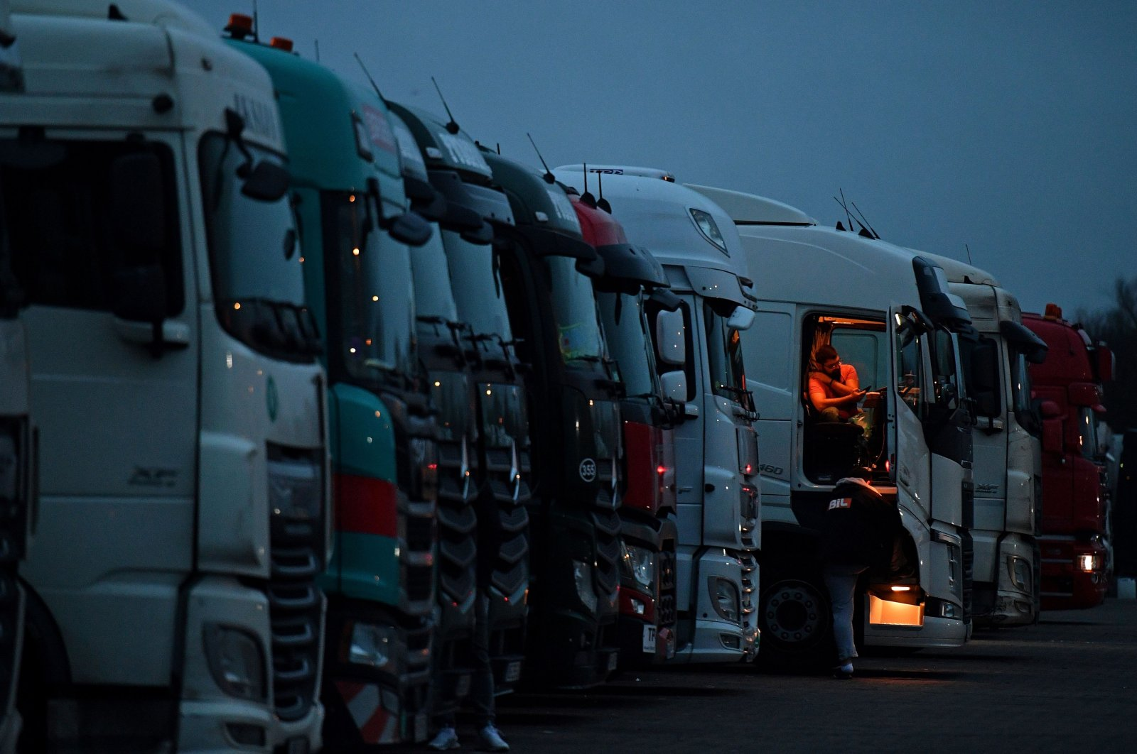 Drivers of freight lorries and heavy goods vehicles are illuminated by the lights inside their cabs as they are parked at a truck stop off the M20 leading to Dover, near Folkestone in Kent, southeast England on Dec. 22, 2020. (AFP Photo)