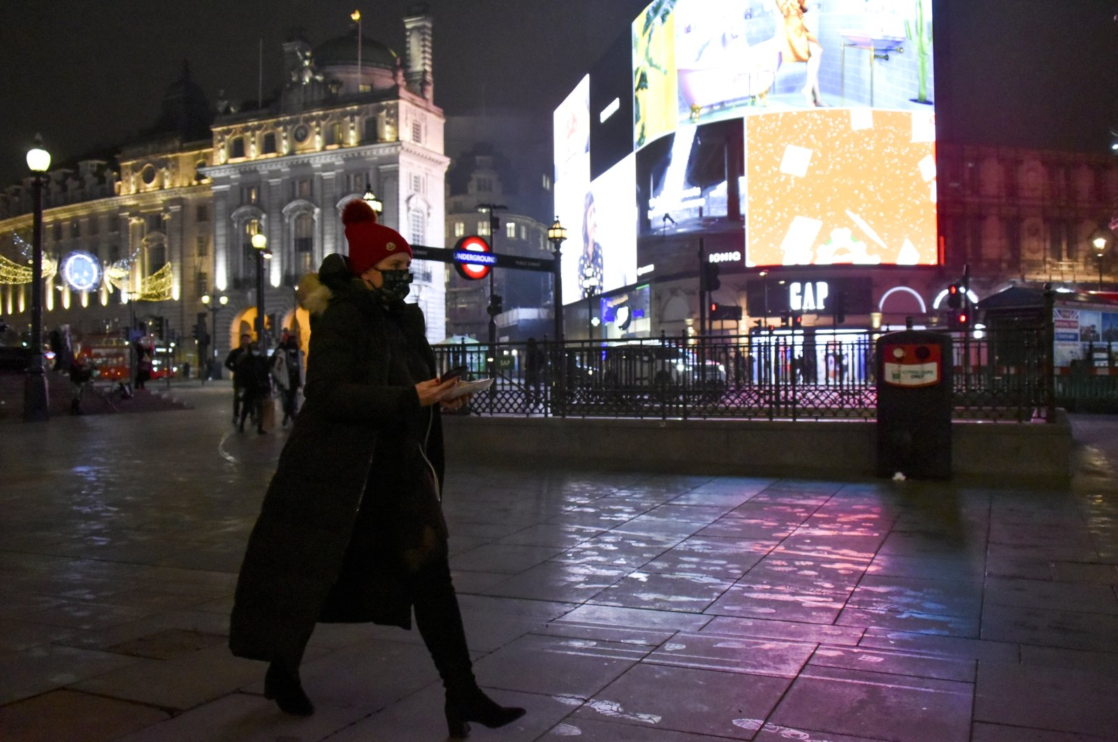 A woman wears a face-covering mask as she walks in the normally busy tourist and shopping area at Piccadilly Circus in London, Dec. 22, 2020. (AP Photo)