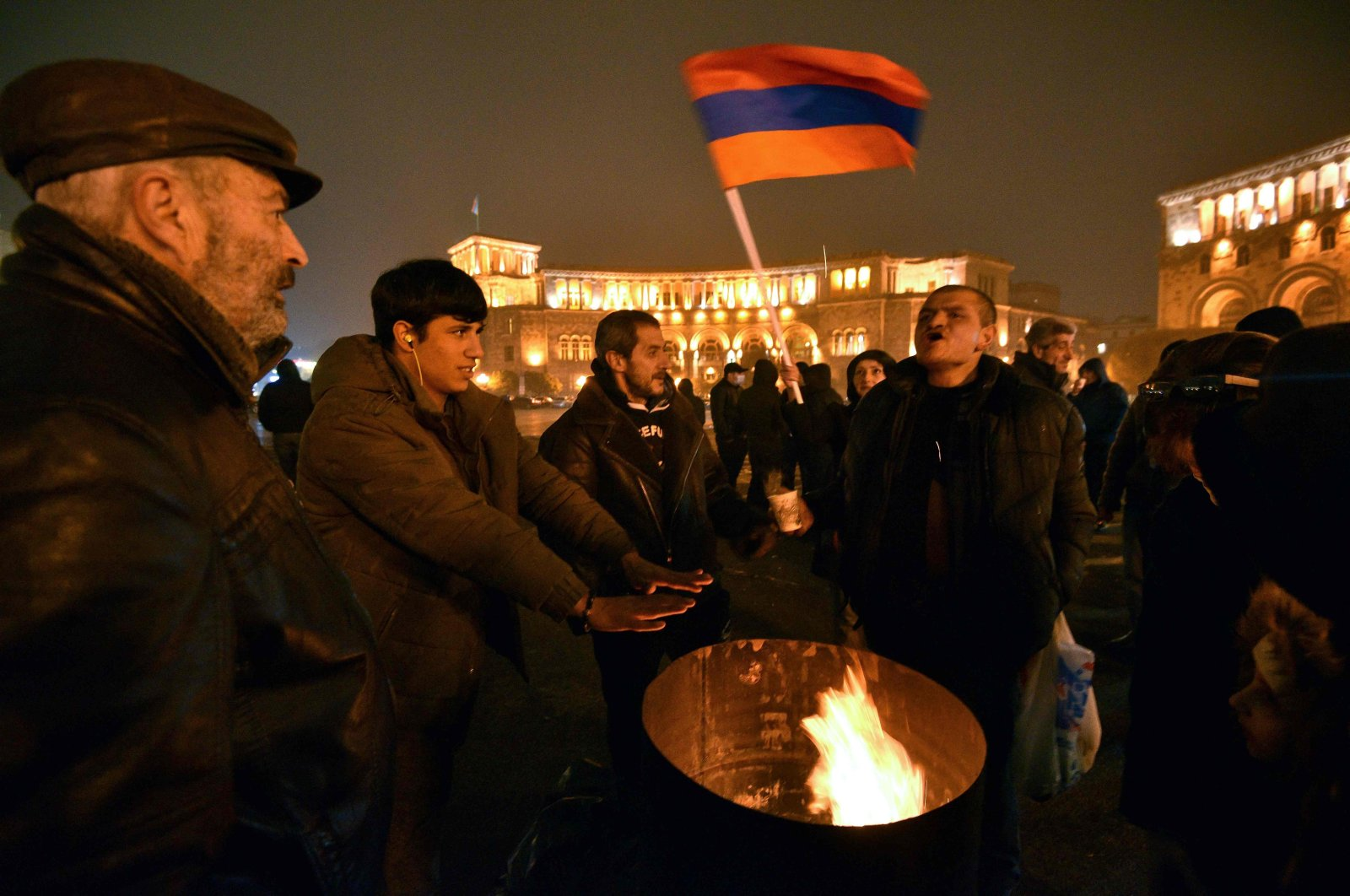 Opposition supporters warm themselves near a bonfire during a rally to demand the resignation of Prime Minister Nikol Pashinyan over the peace deal with Azerbaijan that ended six weeks of war over the disputed region of Nagorno-Karabakh, in Yerevan's Republic Square on Dec. 22, 2020. (AFP Photo)