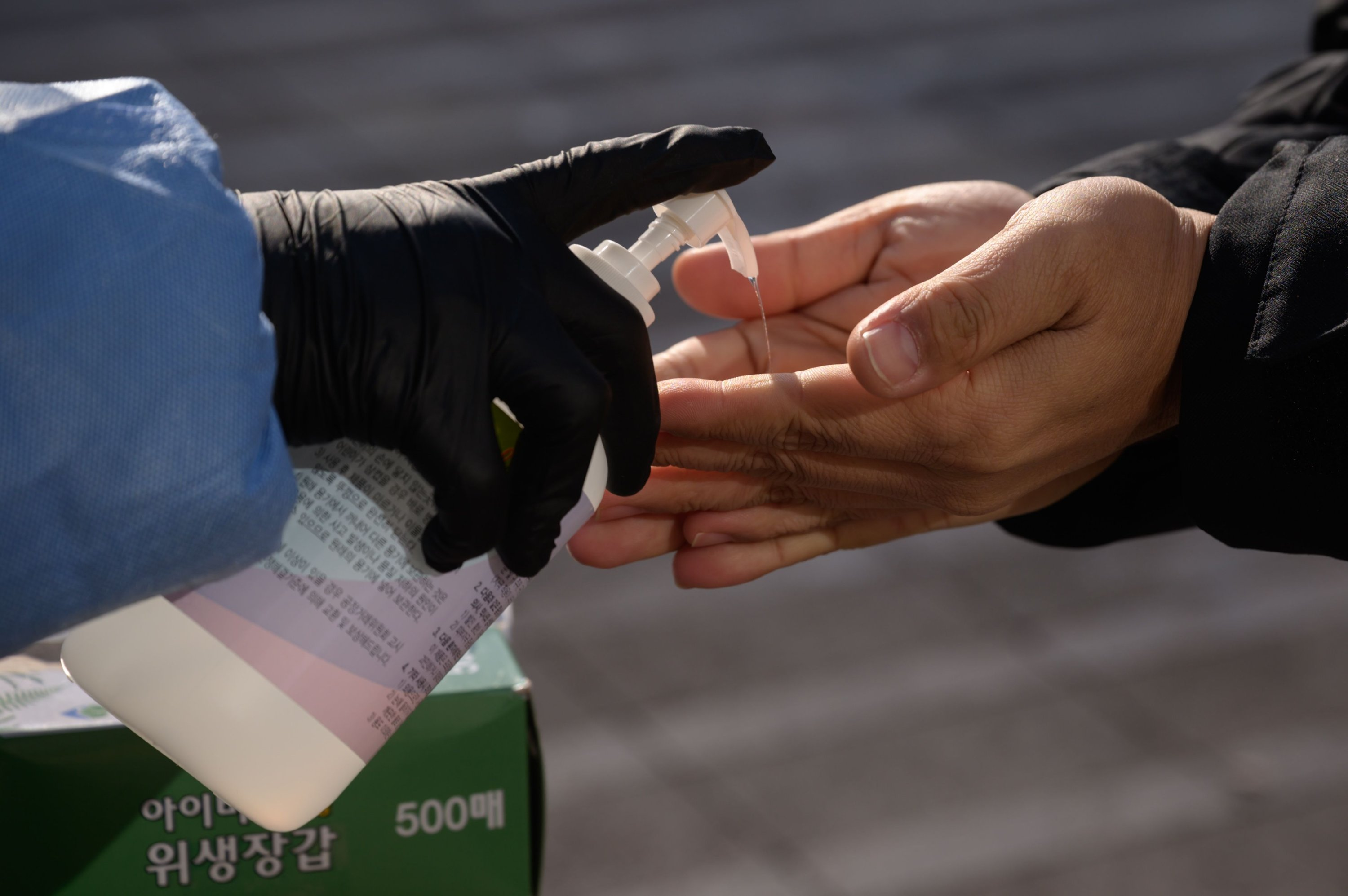 A health worker distributes hand sanitizer prior to people taking a test for the novel coronavirus at a temporary testing center at city hall plaza in Seoul on Dec. 18, 2020. (AFP PHOTO)