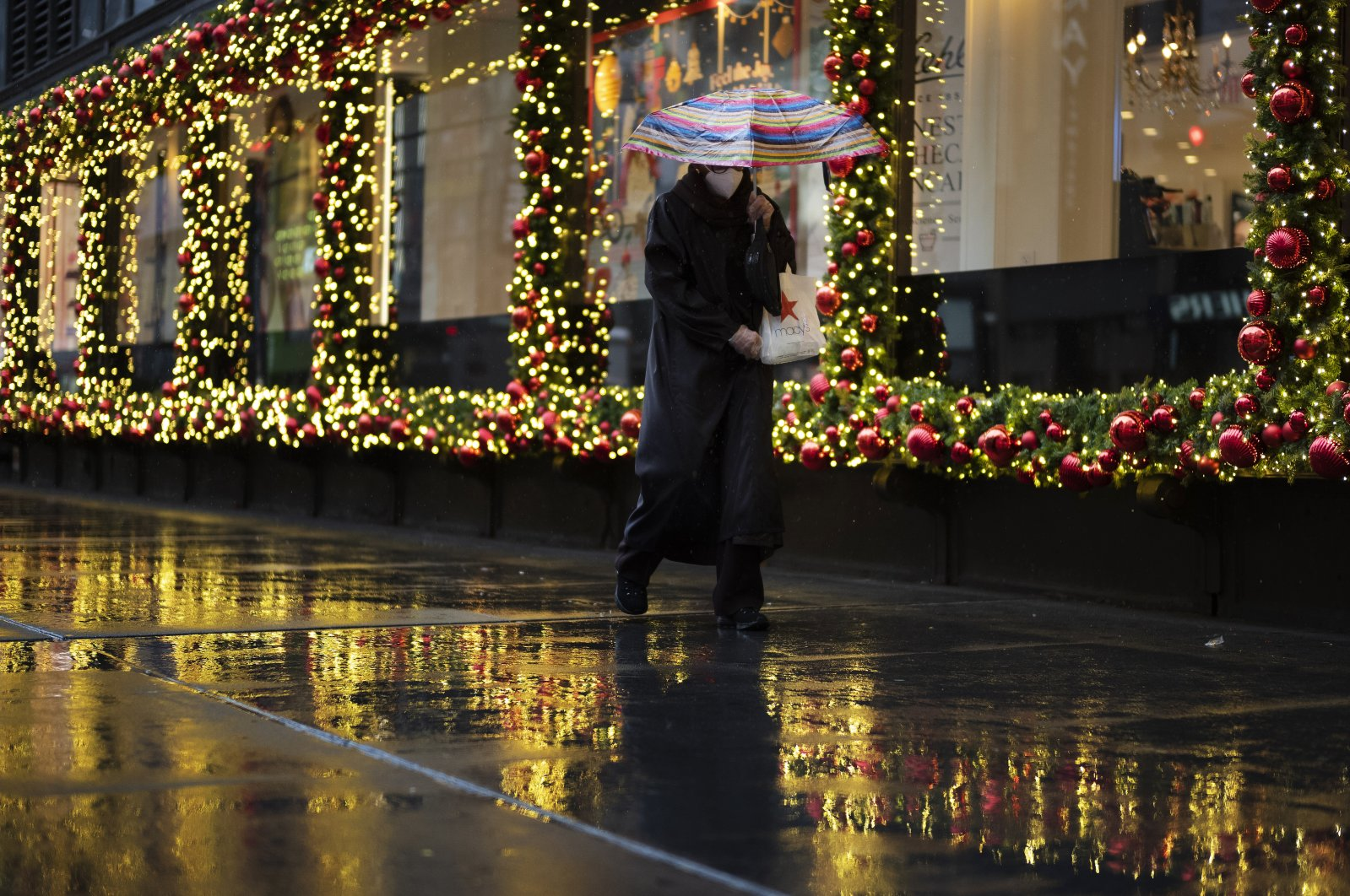 A shopper walks by holiday window displays in New York, U.S., Nov. 30, 2020. (AP Photo)
