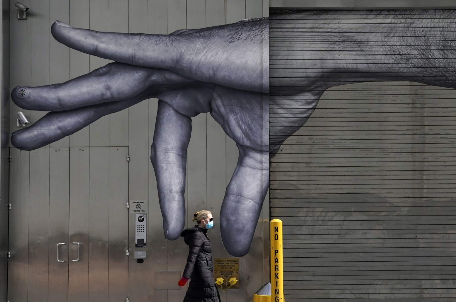 A woman in a mask walks past a mural of a hand on the side of a building in Midtown New York City, Apr. 22, 2020. (AFP PHOTO)