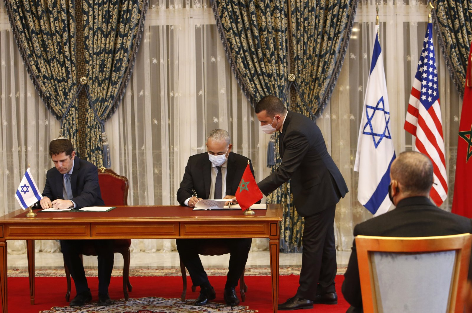 Morocco and Israel sign agreements on direct flights, financial cooperation, visa waivers for diplomats and water technology cooperation at the guest house next to the royal palace in Rabat, Morocco, Dec. 22, 2020. (AP Photo)