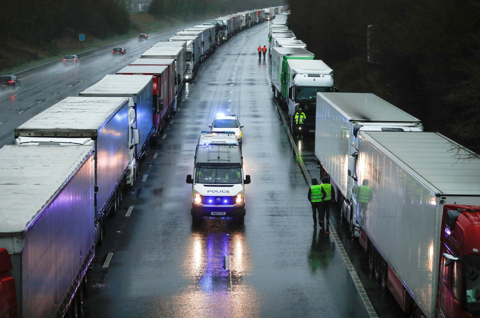 Police cars pass by lorries queueing on M20 motorway to enter port Dover, as EU countries impose a travel ban from the U.K. following the coronavirus outbreak, near Ashford, Britain, Dec. 23, 2020. (Reuters Photo)