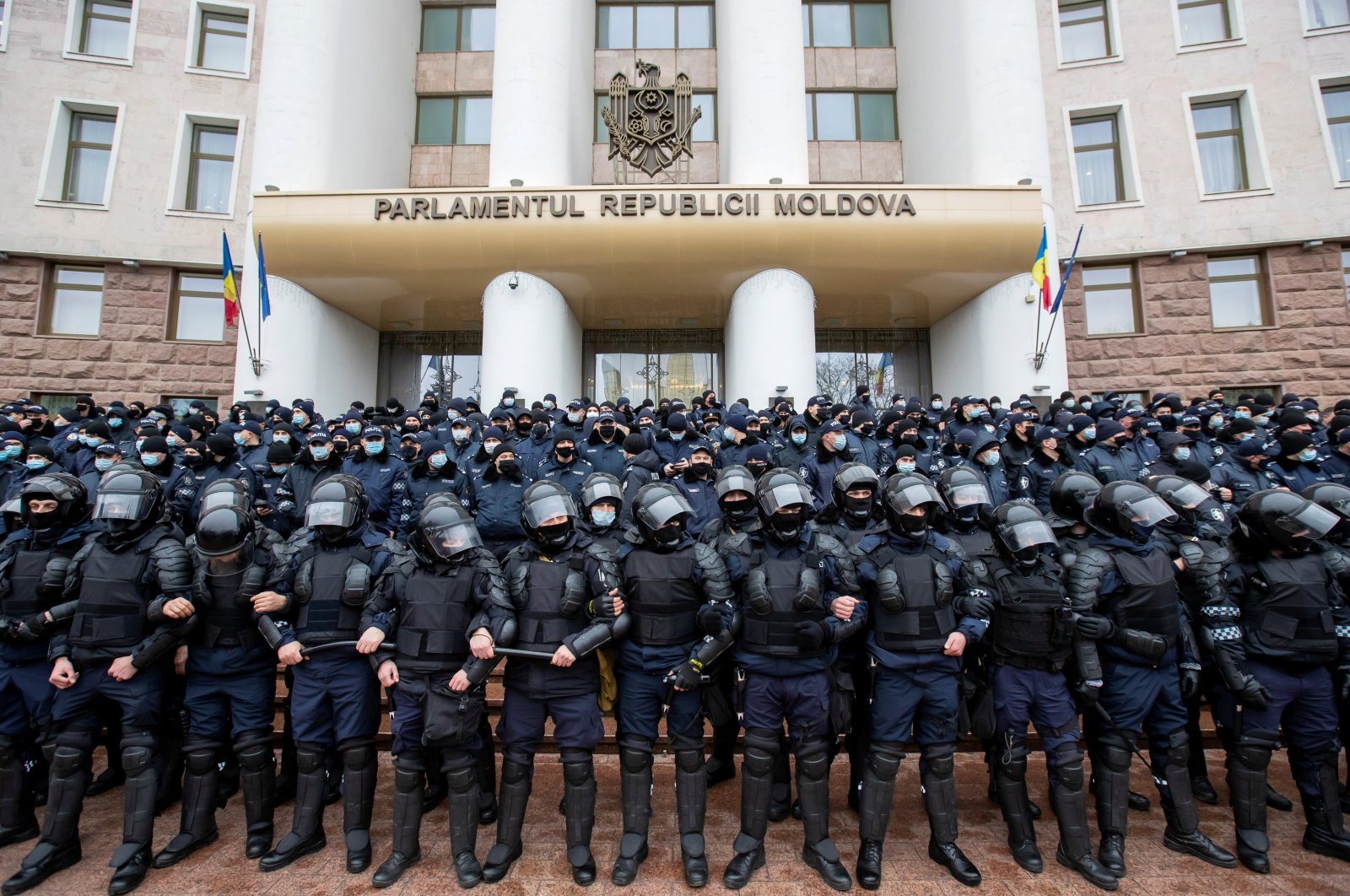 Moldovan law enforcement officers stand guard during a rally of farmers and agrarians, who demand governmental support and financial aid near the parliament building in Chisinau, Moldova, Dec. 16, 2020. (Reuters Photo)