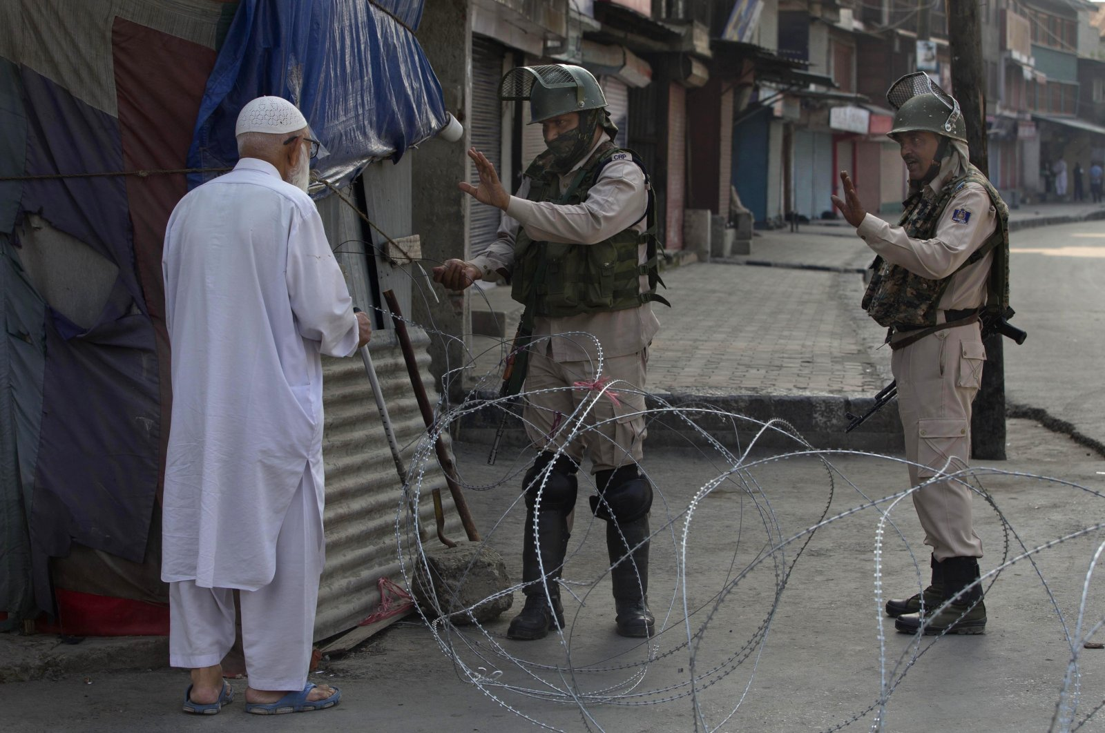 An elderly Kashmiri man is stopped at a temporary checkpoint set up by Indian paramilitary soldiers during a lockdown in Srinagar, Indian-controlled Kashmir, Aug. 23, 2019. (AP Photo)