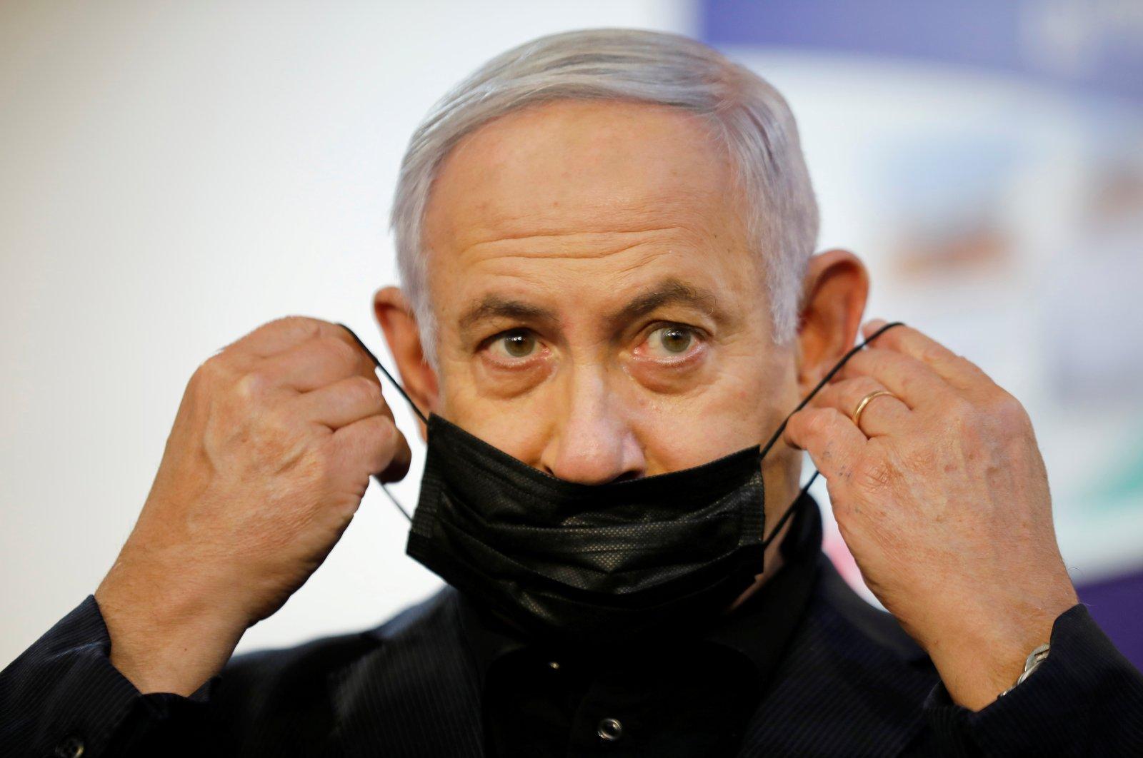 Israeli Prime Minister Benjamin Netanyahu adjusts his protective face mask after receiving a coronavirus vaccine at Sheba Medical Center in Ramat Gan, Israel, on Dec. 19, 2020. (Reuters File Photo)