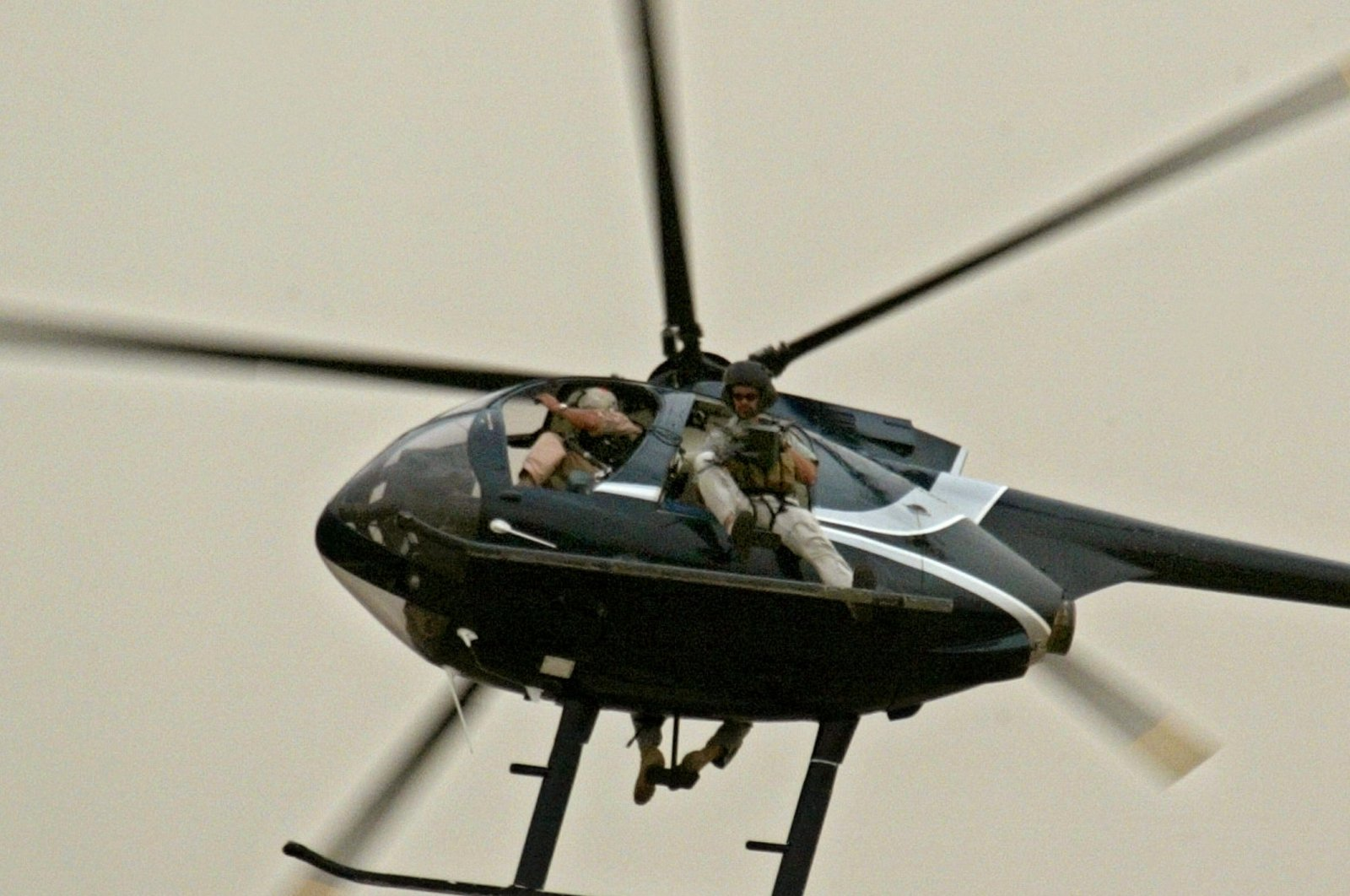 Members of U.S. private security company, Blackwater, patrol the skies of Baghdad on board a Huges 500 helicopter, April 22, 2004 (AFP Photo)