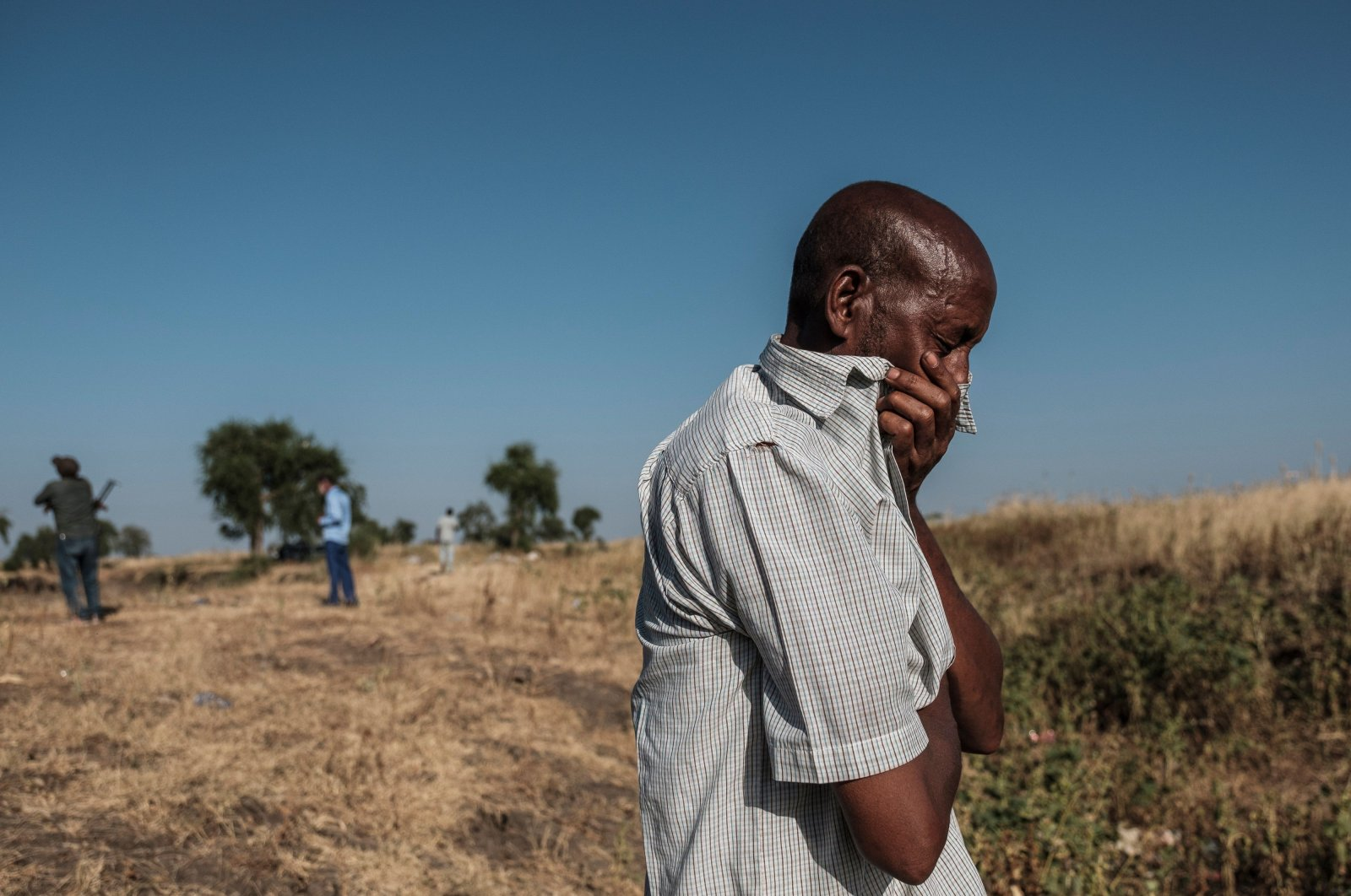 A man reacting as he stands near a ditch in the outskirts of Mai Kadra, Ethiopia, that is filled with more than 20 bodies of victims that were allegedly killed in a massacre, Nov. 21, 2020. (AFP Photo)