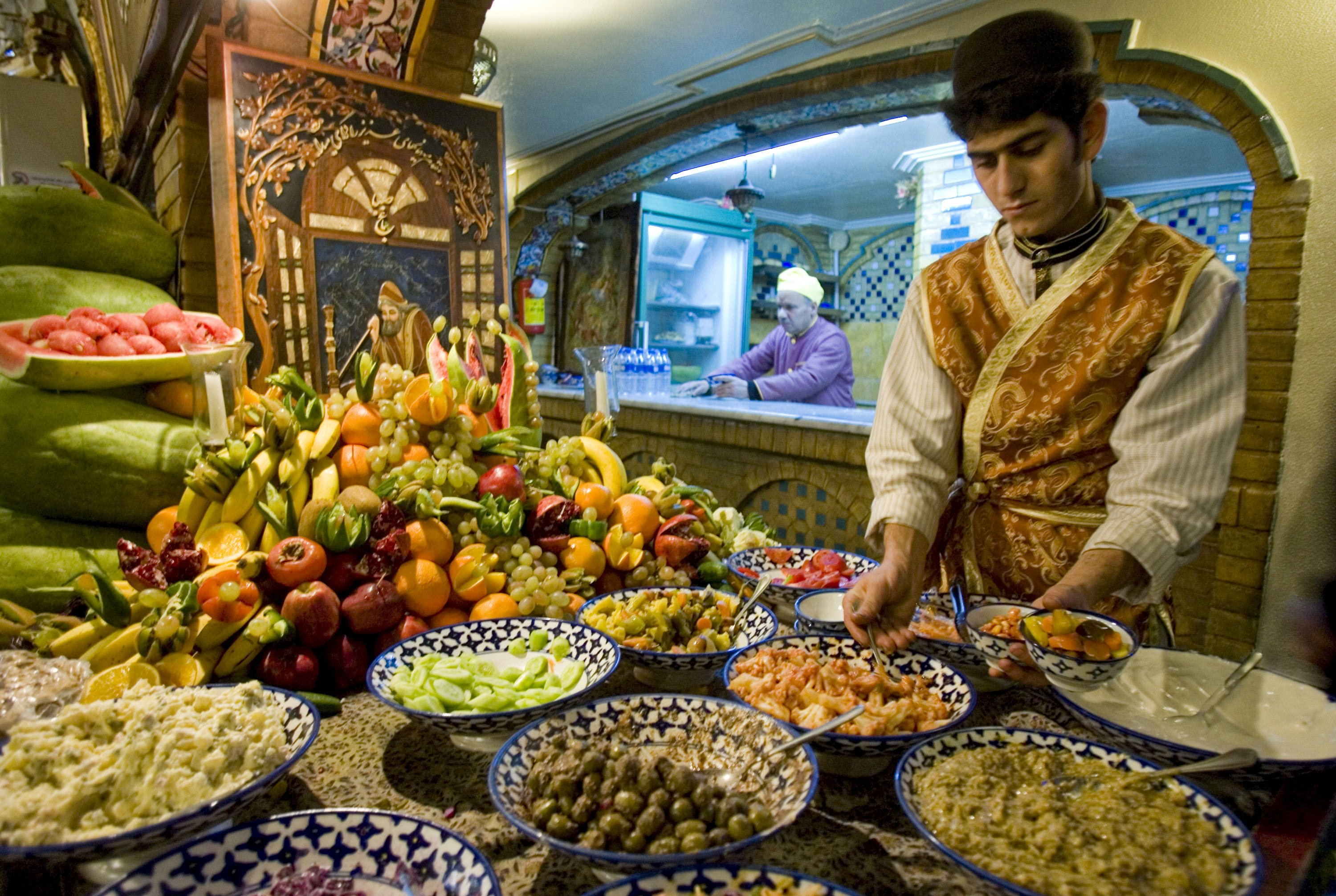 A waiter prepares food to be served to customers at a traditional restaurant during celebrations for the