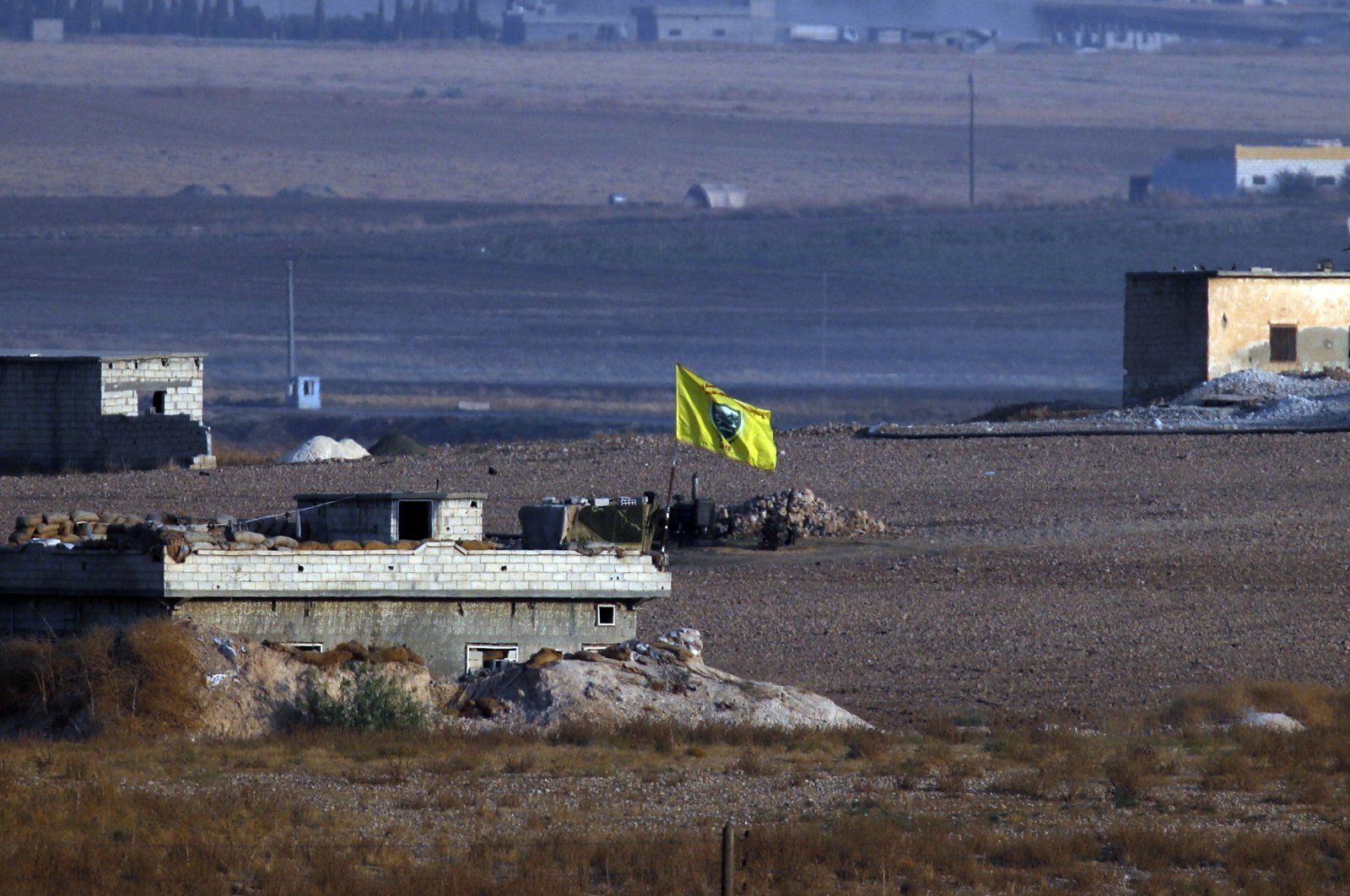 In this photo taken from Akçakale, Şanlıurfa province, southeastern Turkey, shortly after the Turkish operation inside Syria started, a flag of the YPG terrorist group flies on a building on the Syrian side of the border with Turkey, Oct. 9, 2019. (AP Photo)