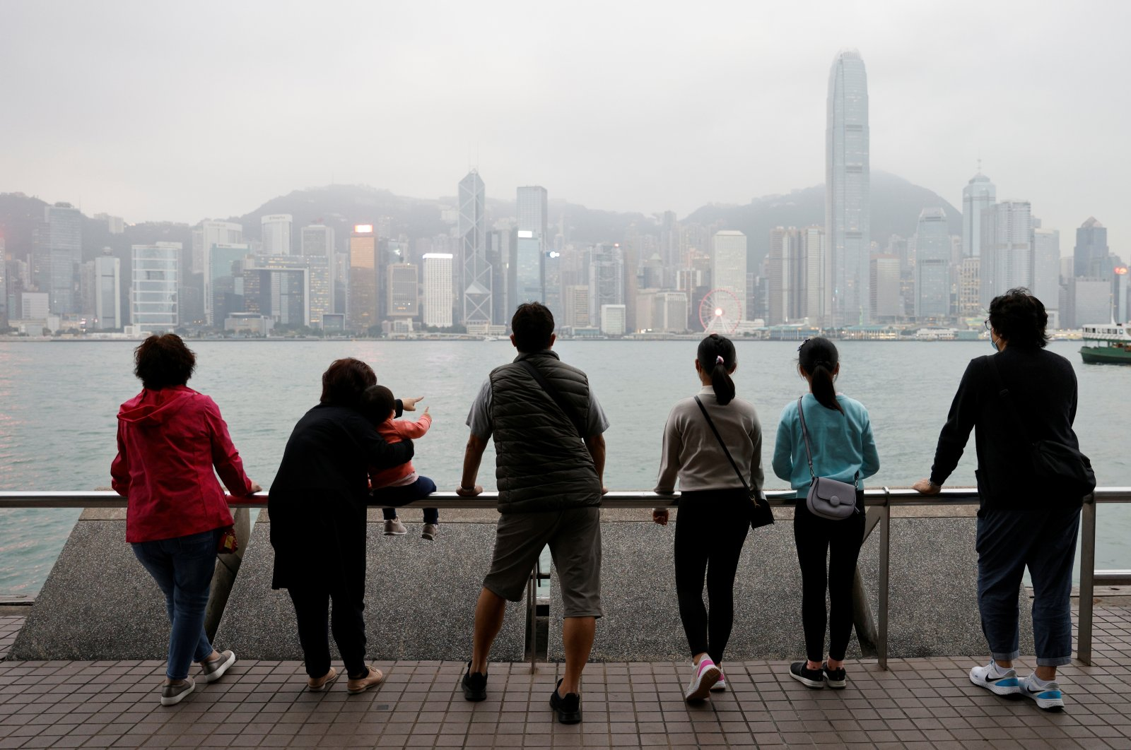 The Lai family, who are emigrating to Scotland, look out over the city's skyline on a outing to Tsim Sha Tsui in Hong Kong, China, Dec. 14, 2020. (Reuters Photo)