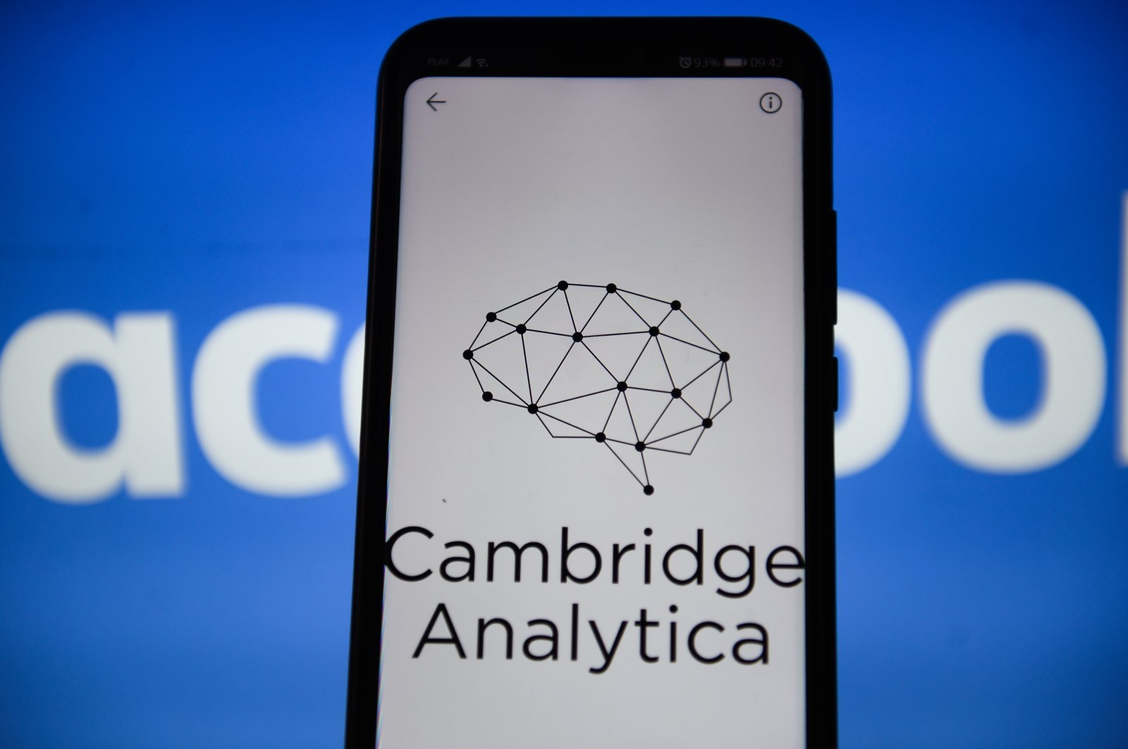 In this photo illustration, a Cambridge Analytica logo on a smartphone is held in front of a Facebook background, Sept. 24, 2019. (Photo by Getty Images)