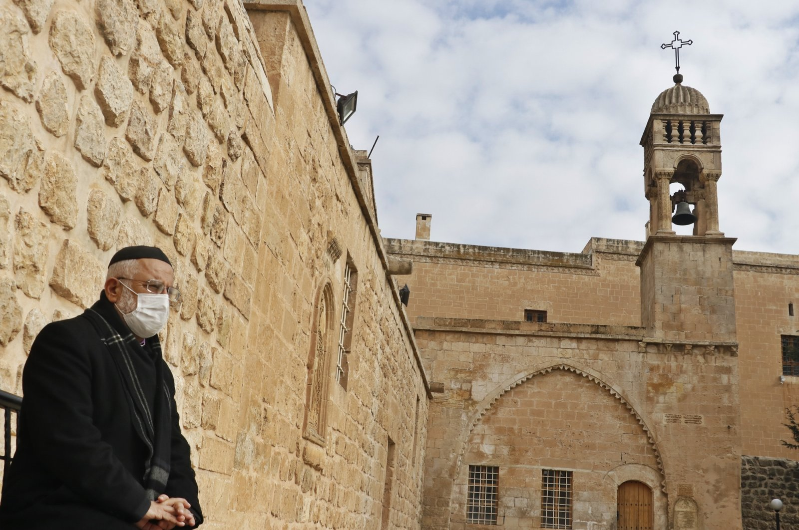 Priest Gabriel Akyüz stands next to Kırklar Church where a Christmas service will be held with only 50 people, in Mardin, southeastern Turkey, Dec. 23, 2020. (DHA PHOTO)