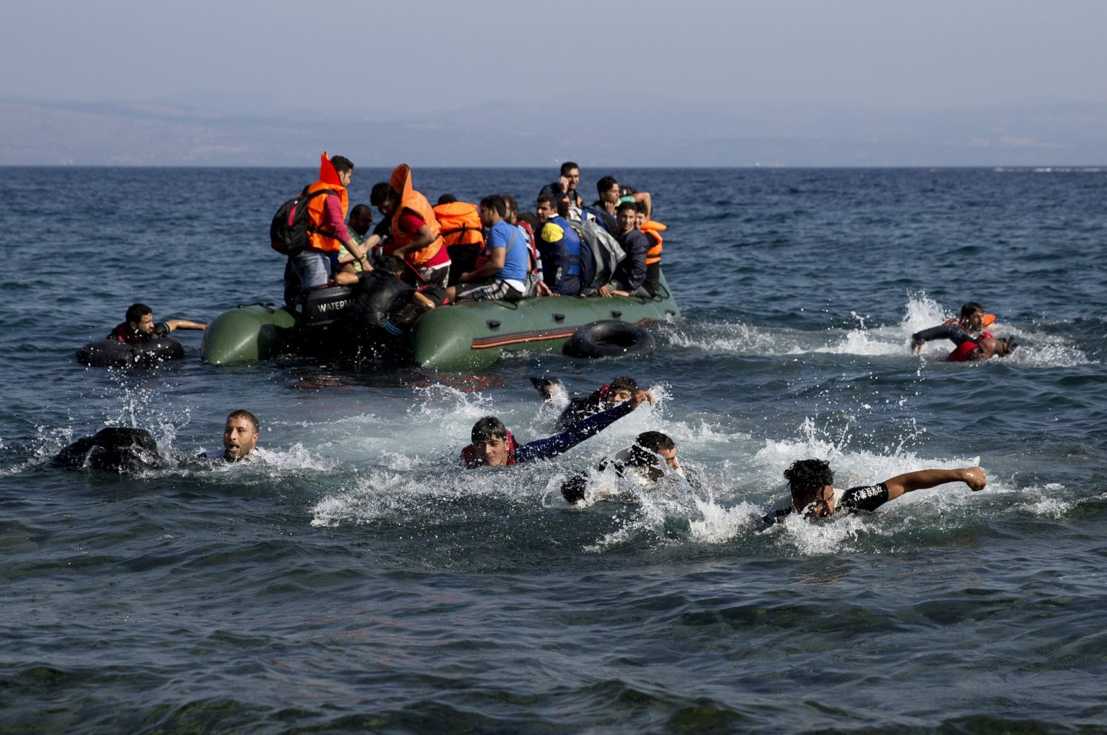 Migrants whose boat stalled at sea while crossing from Turkey to Greece swim toward the shore of the island of Lesbos, Greece, Sept. 20, 2015. (AP Photo)