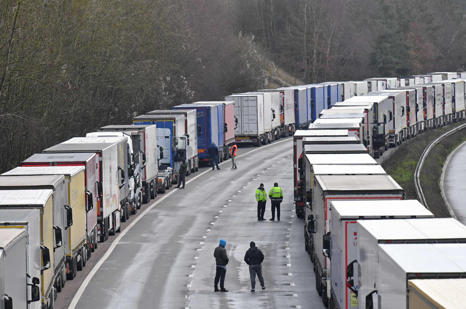 Freight lorries remain lined up on the M20 motorway, southbound, leading to the Port of Dover at Mersham in southeast England, Dec. 24, 2020, as rail and sea links between the U.K. and France are to remain open over Christmas to clear the backlog of thousands of trucks stranded by a new strain of the coronavirus. (AFP Photo)