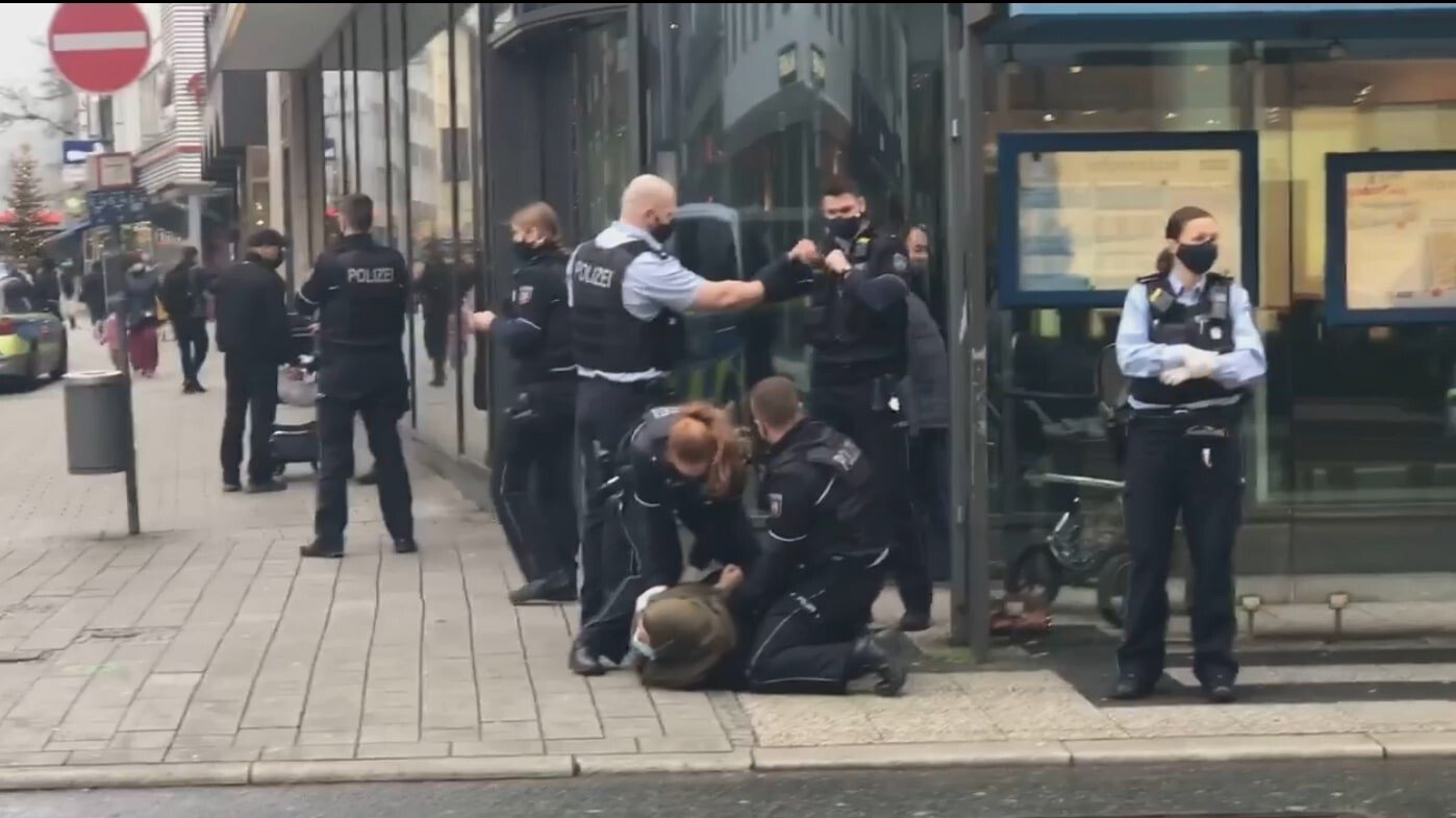 This screengrab from a footage captured by a bystander shows police officers violently arresting a Muslim woman in front of her toddler for not wearing mask in Wuppertal, Germany. (IHA Photo)