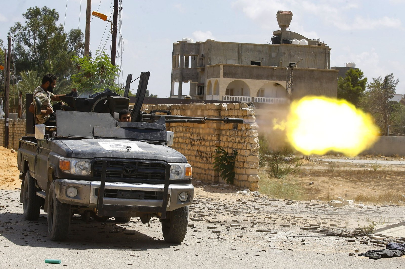 In this file photo taken on September 7, 2019, a fighter loyal to the internationally-recognized Libyan Government of National Accord (GNA) fires a truck-mounted gun during clashes with forces loyal to putschist Gen. Khalifa Haftar in the capital Tripoli's suburb of Ain Zara. (AFP File Photo)