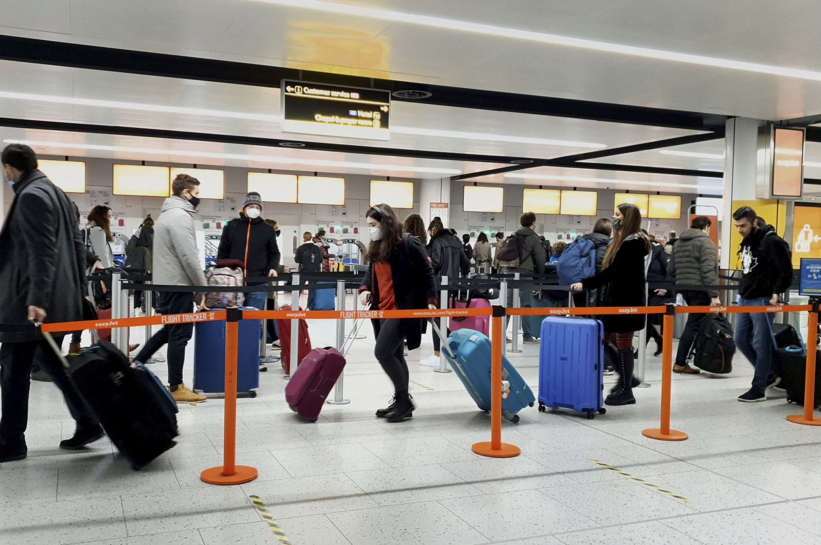 Passengers queue for check-in at Gatwick Airport in West Sussex, south of London, Britain, Dec. 20, 2020. (AP Photo)