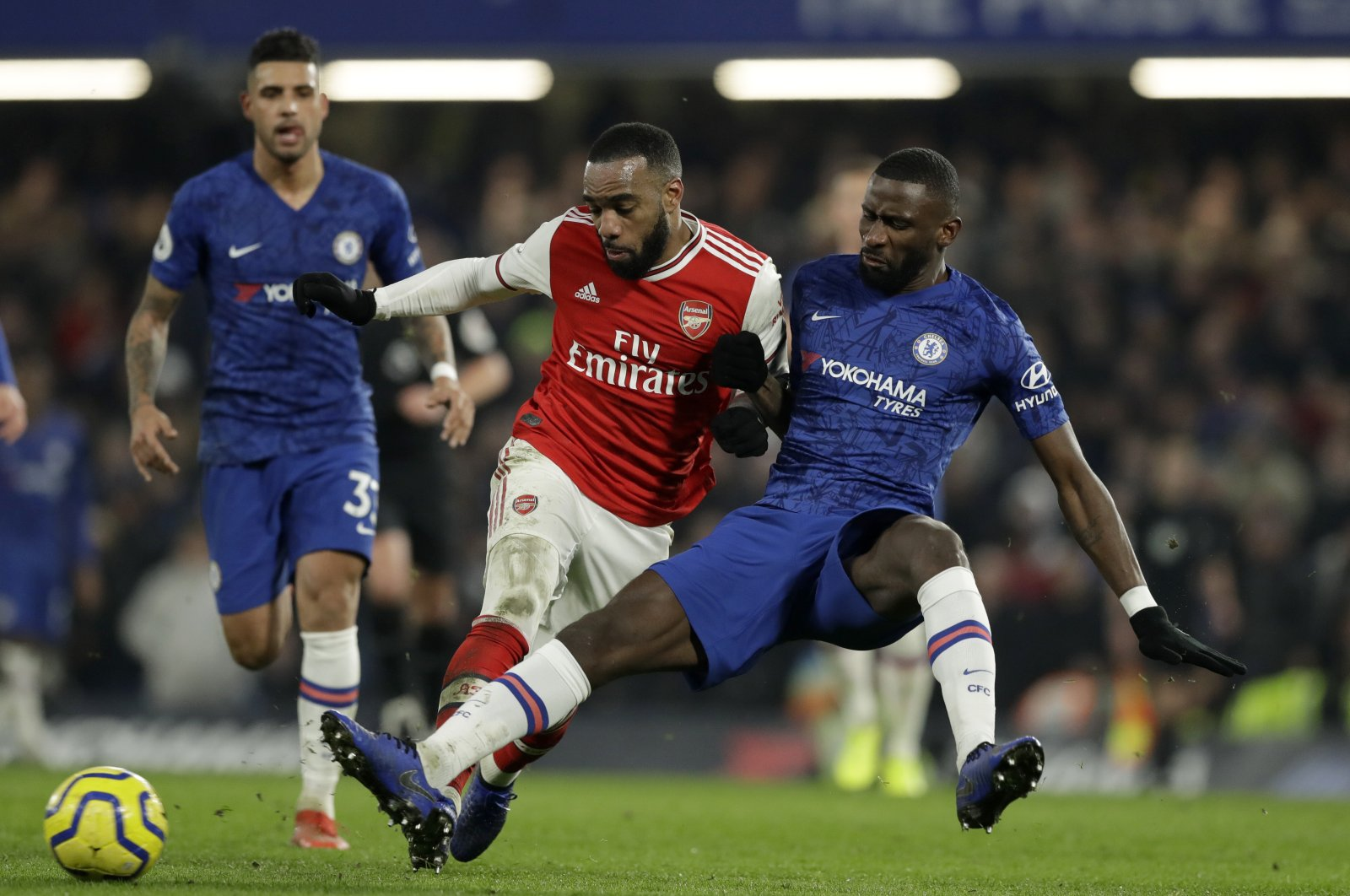 Arsenal's Alexandre Lacazette (C) duels for the ball with Chelsea's Antonio Rudiger during a Premier League match at Stamford Bridge Stadium in London, Britain, Jan. 21, 2020. (AP Photo)