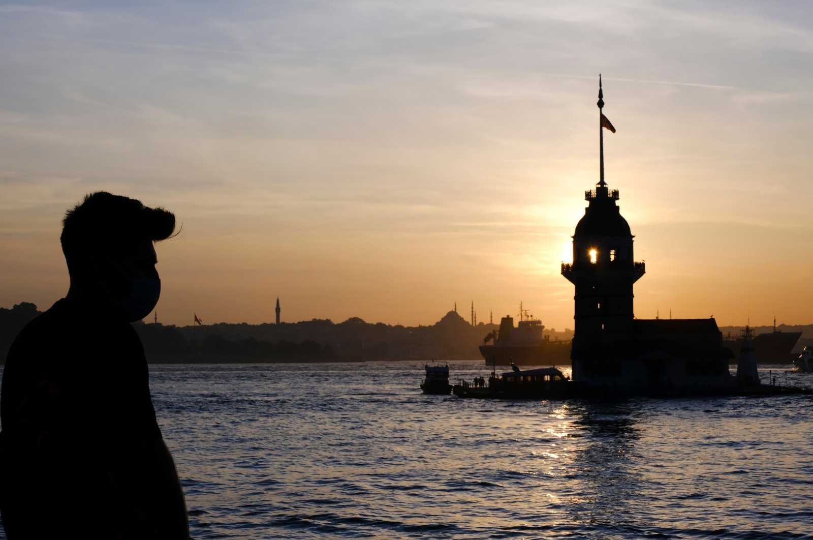 A young man, seen silhouetted, wears a mask to protect against the coronavirus as he stands in front of Maiden's Tower, Istanbul, Turkey. (Shutterstock Photo)
