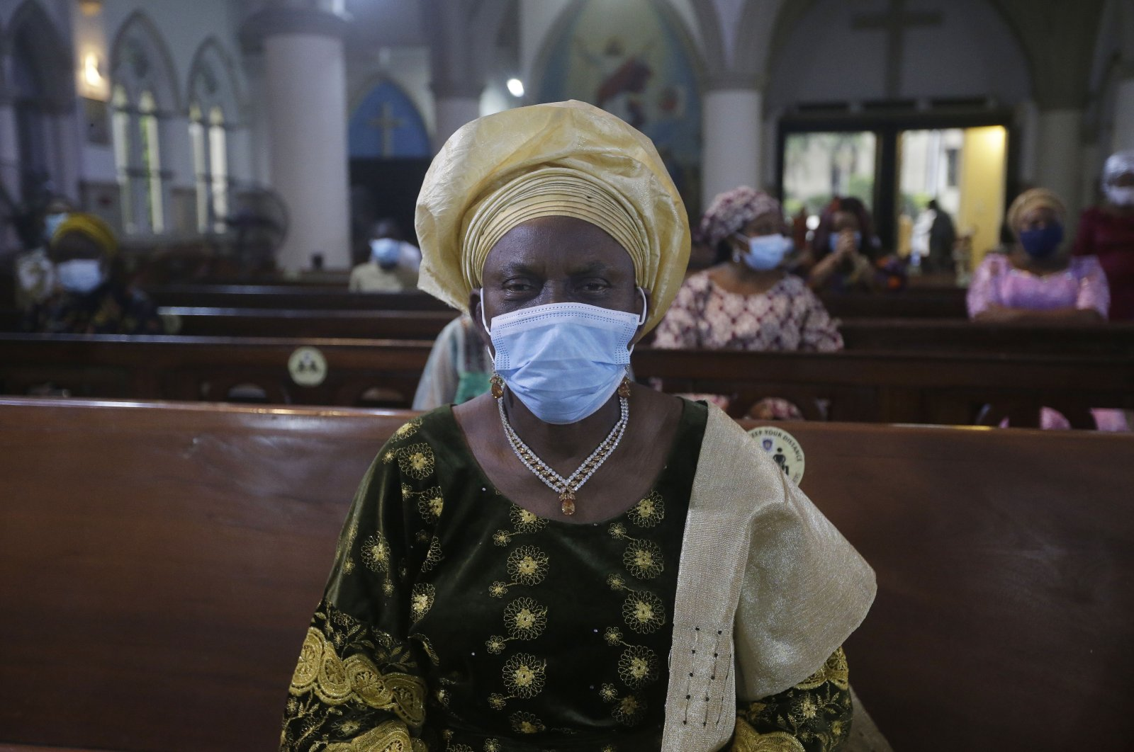 A parishioner wearing face mask to protect against coronavirus, attends a morning Christmas Mass at Holy Cross Cathedral in Lagos, Nigeria, Friday Dec. 25, 2020. (AP Photo)