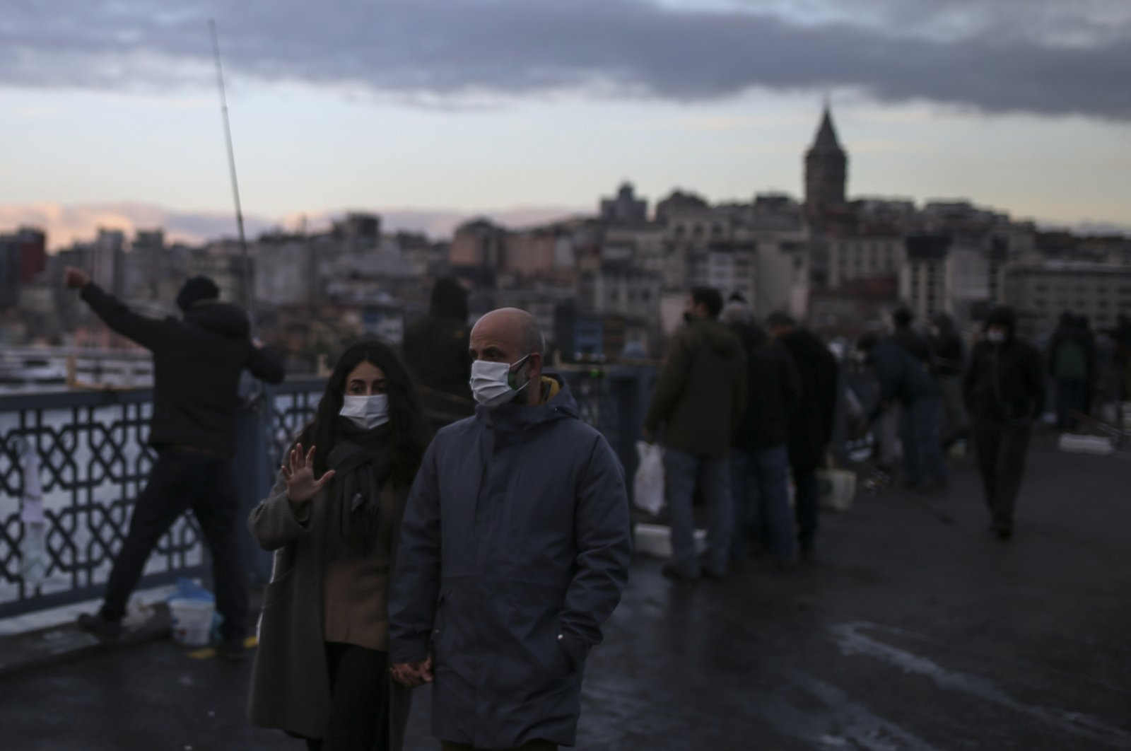 People, wearing protective masks to help curb the spread of the coronavirus, walk on the Galata Bridge over the Golden Horn in Istanbul, Monday, Dec. 21, 2020. (AP)