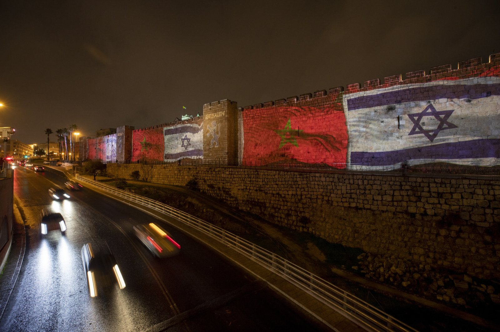 Israelis passing by the walls of Jerusalem's Old City next to Jaffa gate lit up with the Israeli and Moroccan flags as a message of peace, Jerusalem, Dec. 23, 2020. (EPA Photo)
