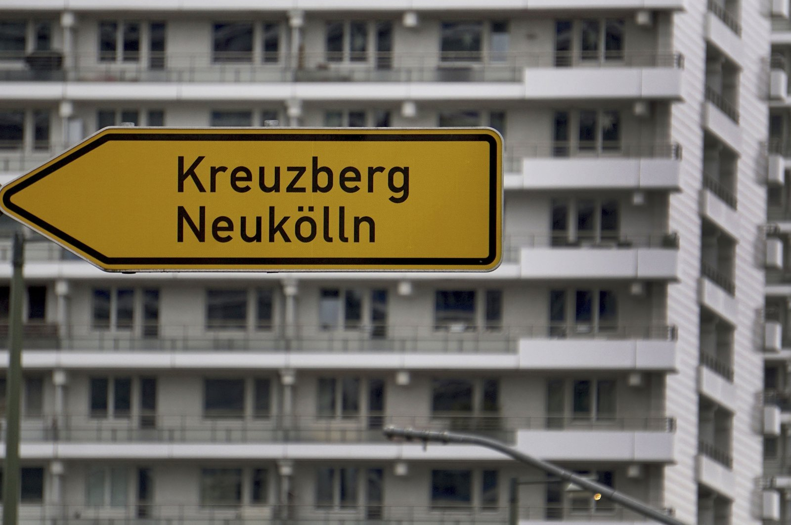 A traffic sign pointing to the Berlin districts of Neukolln and Kreuzberg in front of apartment buildings at the Leipziger Strasse between the Potsdamer Platz (Potsdam Square) and the Alexander Platz (Alexander Square) in Berlin, Germany, Jan. 30, 2020. (AP Photo)