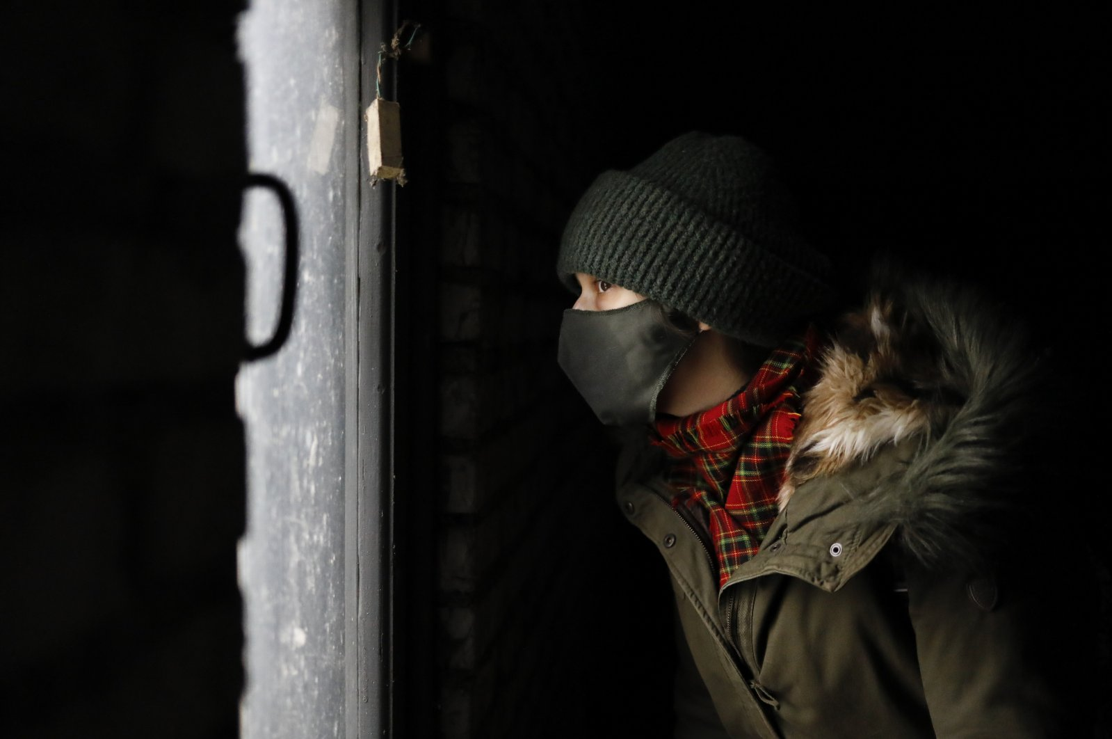 A young demonstrator wearing a face mask to help curb the spread of the coronavirus looks out of a dark garage where he is hiding from the police during an opposition rally to protest the official presidential election results in Minsk, Belarus, Dec. 13, 2020.  Crowds of people took to the streets of the Belarusian capital on Sunday, in a traditional weekly protest against the country's authoritarian leader who won a sixth term in office in a disputed election. Small rallies were scattered around more than 70 different areas of Minsk. (AP Photo)