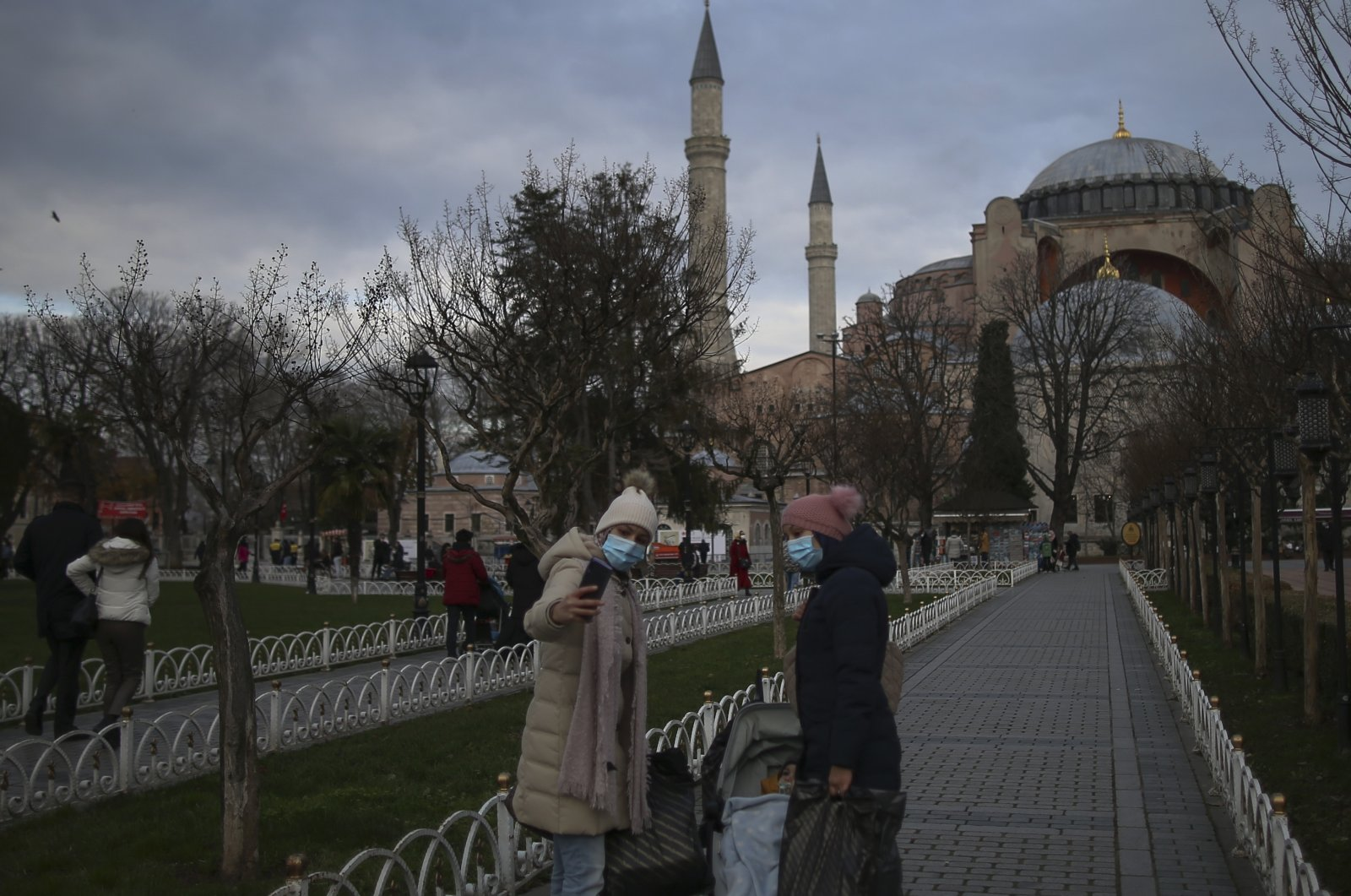 Backdropped by the Byzantine-era Hagia Sophia, people, wearing protective masks to help curb the spread of the coronavirus, take pictures on the historic Sultanahmet district of Istanbul, Dec. 21, 2020. (AP Photo)