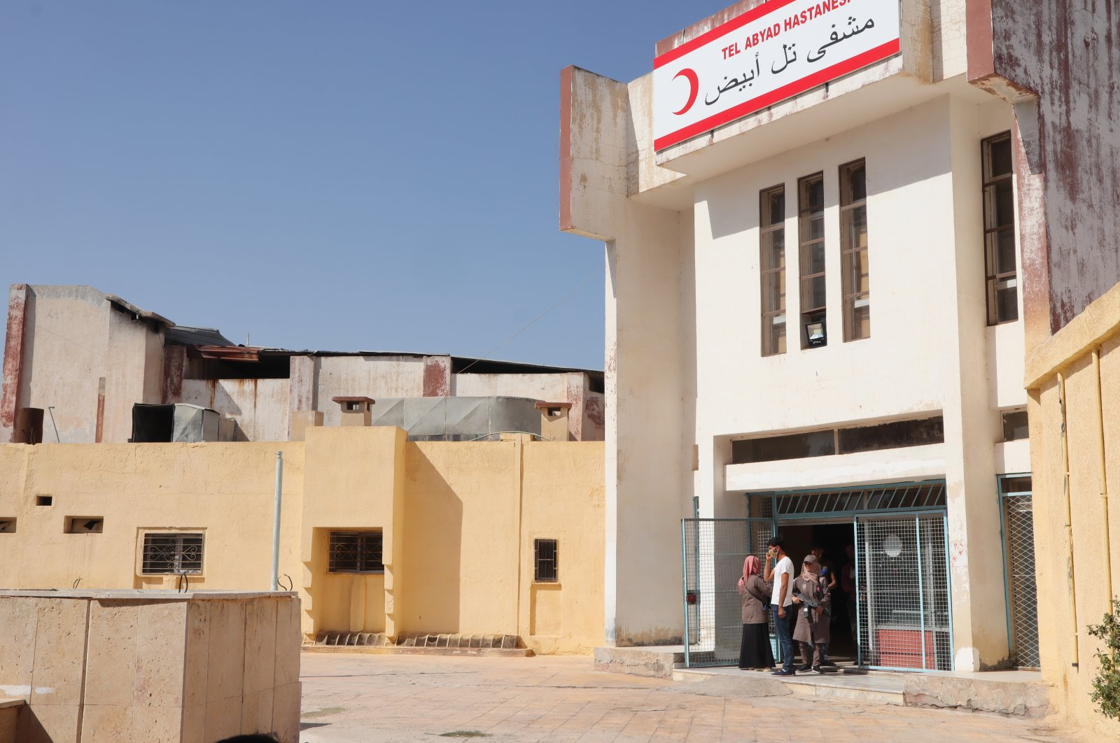 People wait in front of the hospital in northern Syria's Tal Abyad, Oct. 11, 2020. (Photo by Dilara Aslan)