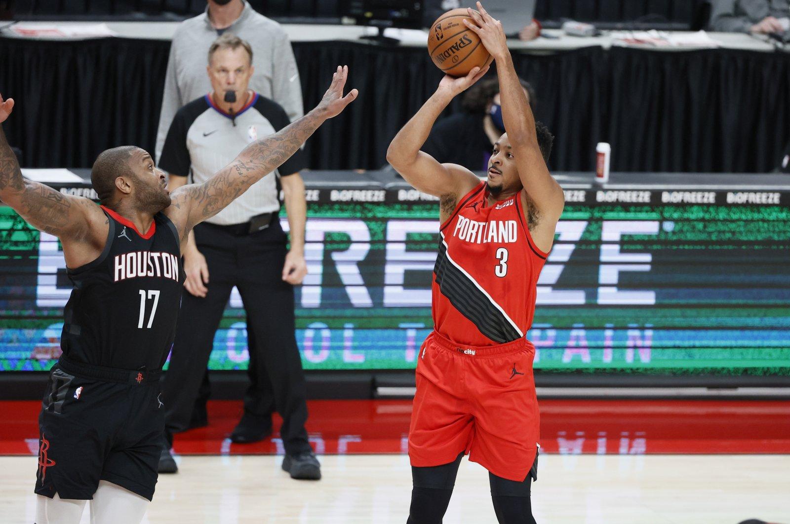 Portland Trail Blazers' CJ McCollum (R) shoots over Houston Rockets' P.J. Tucker during an NBA game at the Moda Center in Portland, Oregon, U.S., Dec. 26, 2020. (Reuters Photo)