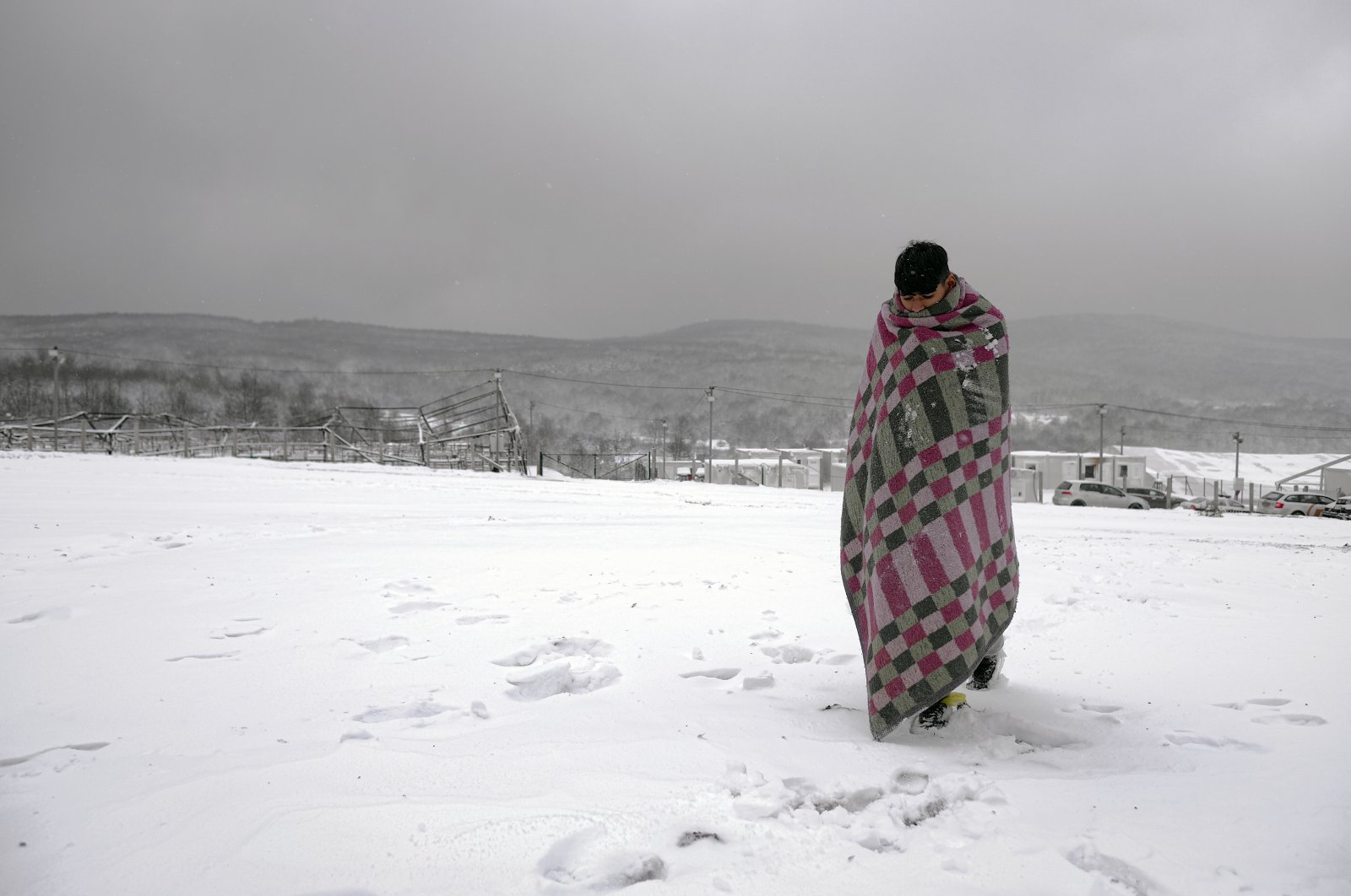 A migrant walks through the snow wrapped in a blanket at the Lipa camp in northwestern Bosnia, near the border with Croatia, Dec. 26, 2020. (AP Photo)