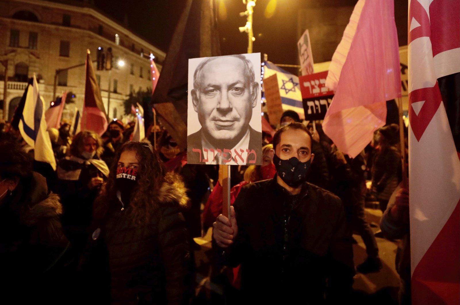 Israeli protesters hold signs during a demonstration against Israeli Prime Minister Benjamin Netanyahu in Jerusalem, Saturday, Dec. 26, 2020. (AP Photo)