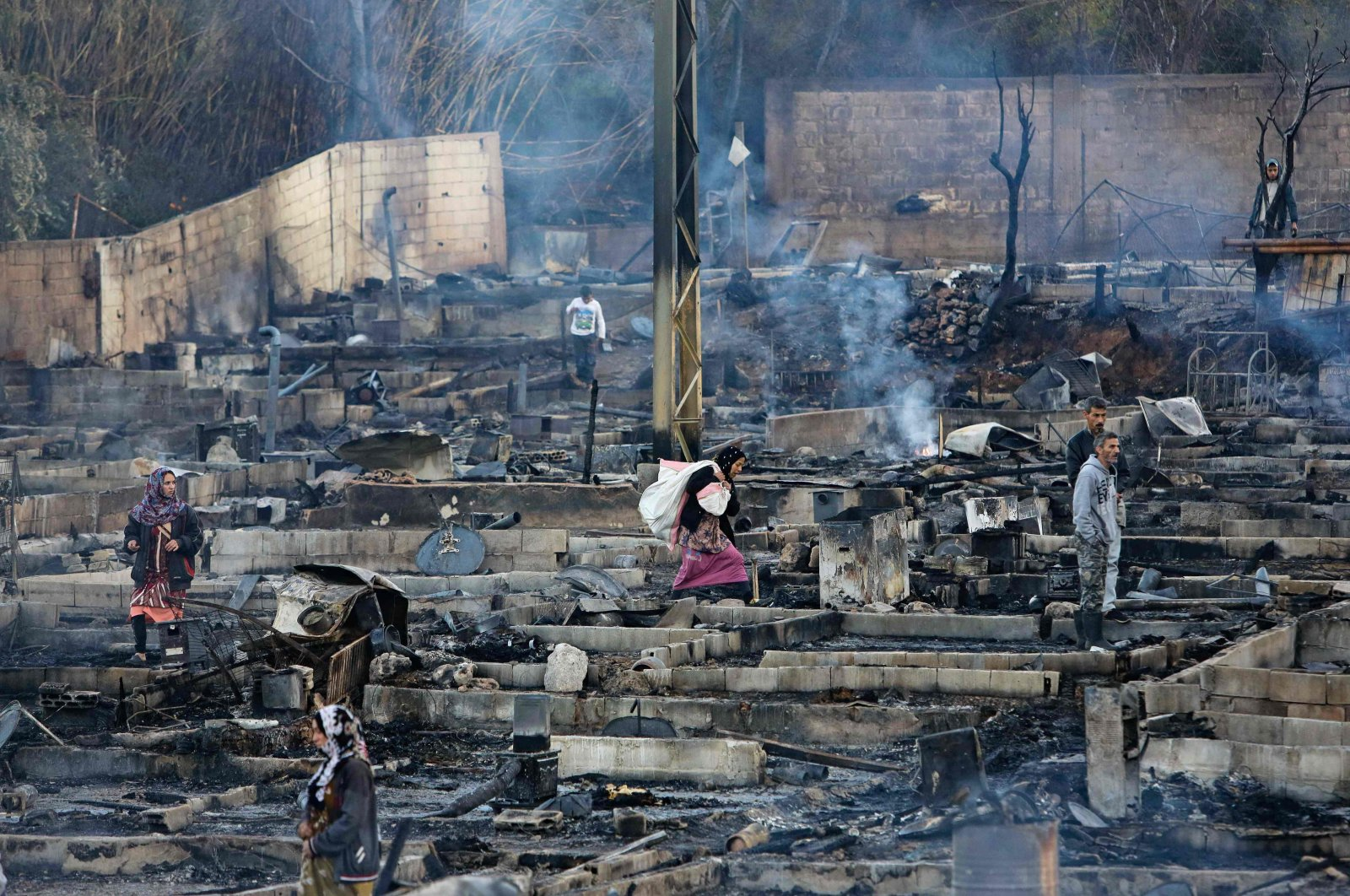 Syrian refugees salvage belongings from the wreckage of their shelters at a camp set on fire overnight in the northern Lebanese town of Bhanine following a fight between members of the camp and a local Lebanese family, Dec. 27, 2020. (AFP Photo)